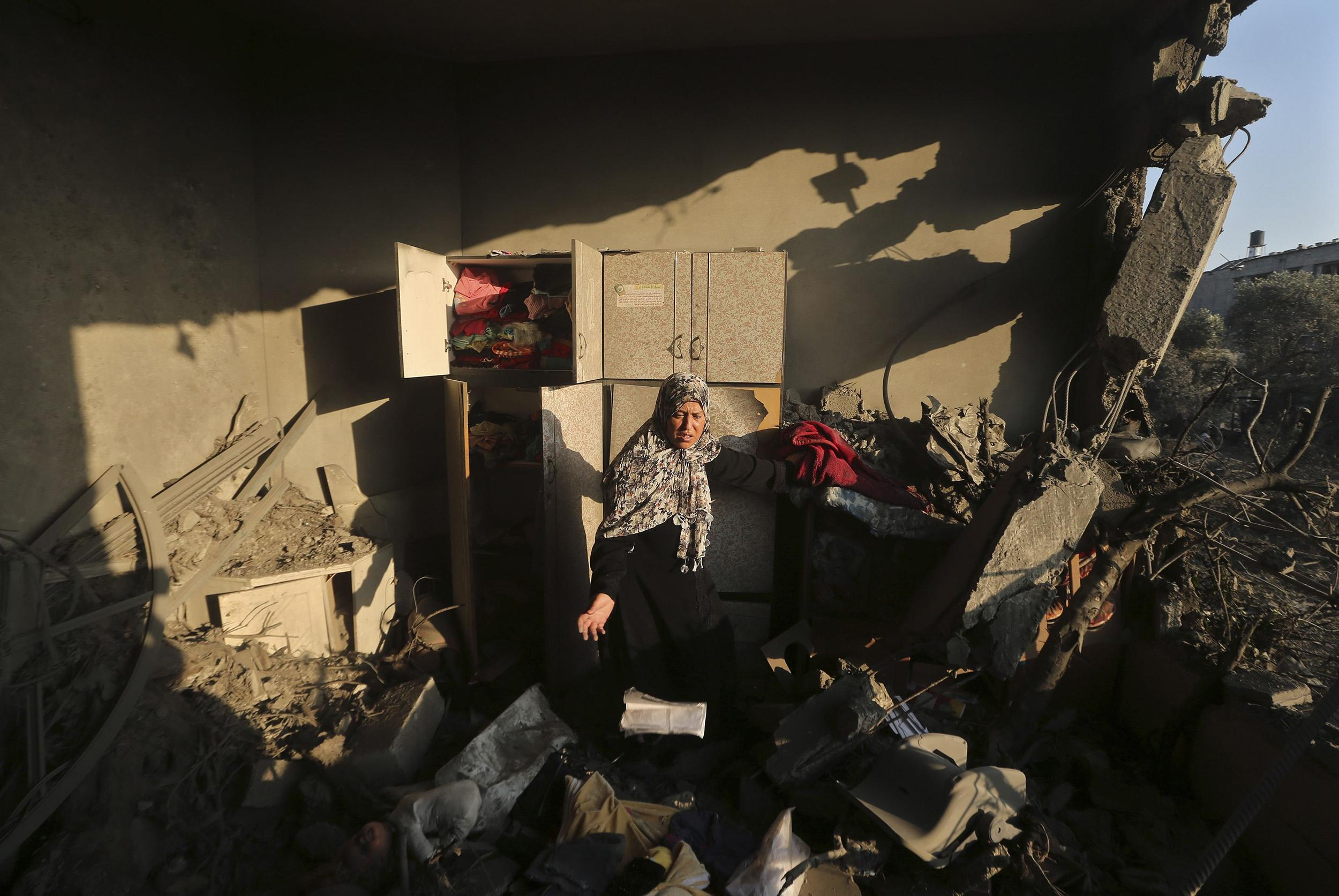 Image: Palestinian woman inspects her house which police said was damaged in an Israeli air strike on a neighbouring house in Gaza City