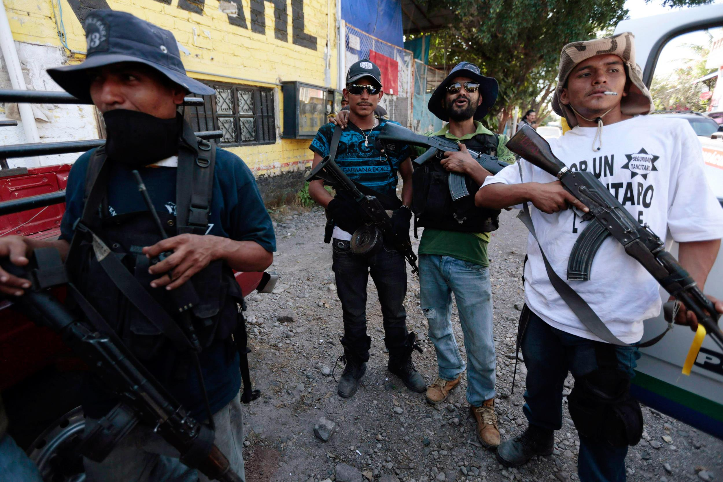 Image: Members of the community police, acting in this case as vigilantes, stand together after breaking into and taking over the village of Paracuaro in Michoacan state