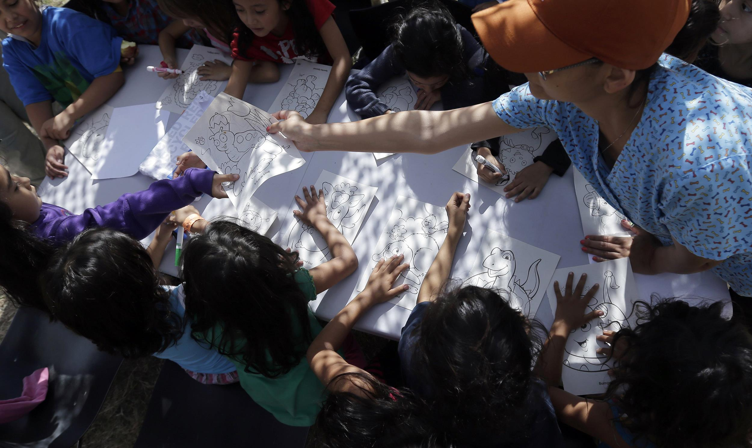 Image: Detainees color and draw at a U.S. Customs and Border Protection processing facility