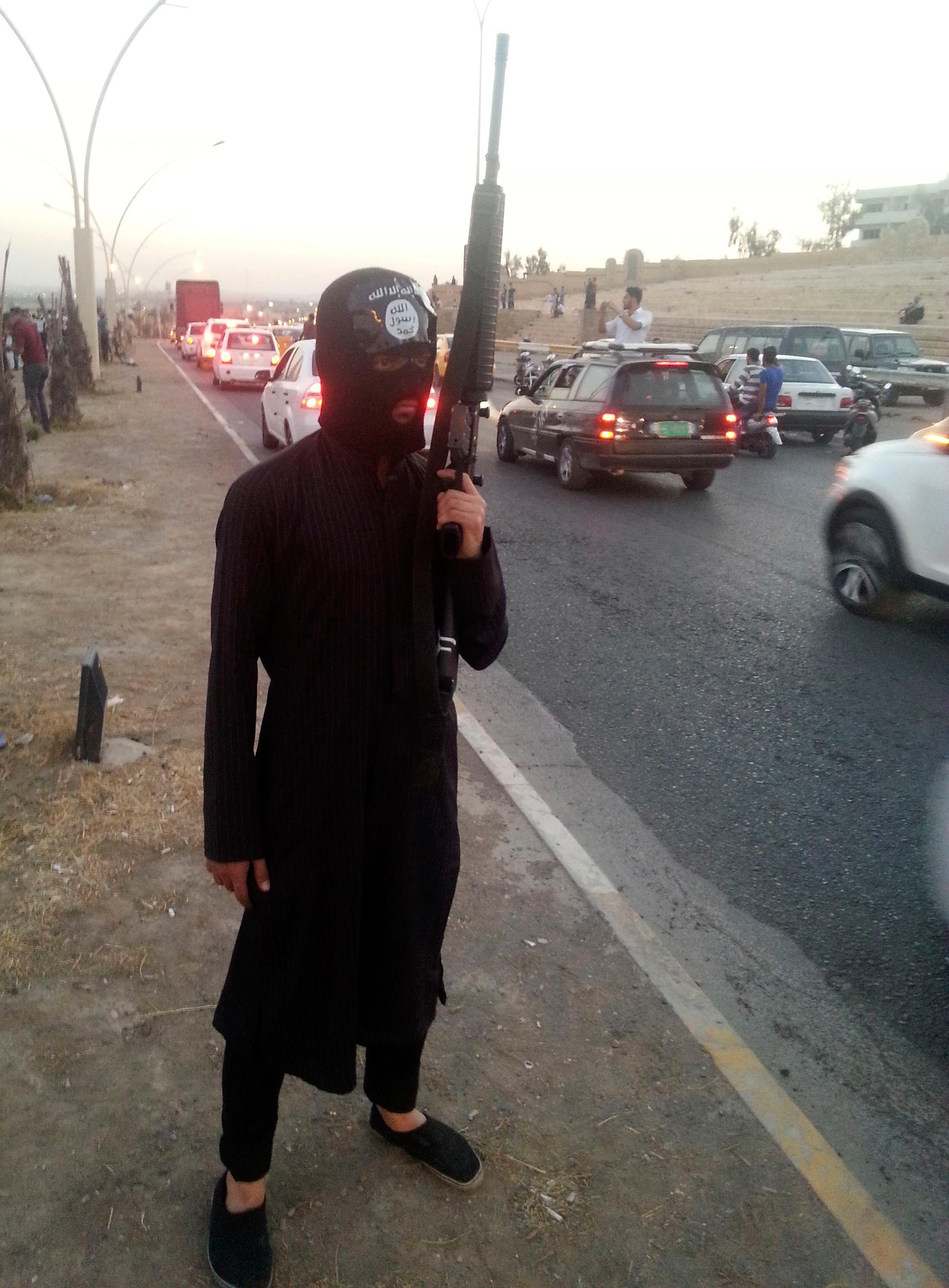 Image: An ISIS fighter stands guard with his weapon by the side of a street in the city of Mosul, June 23, 2014.