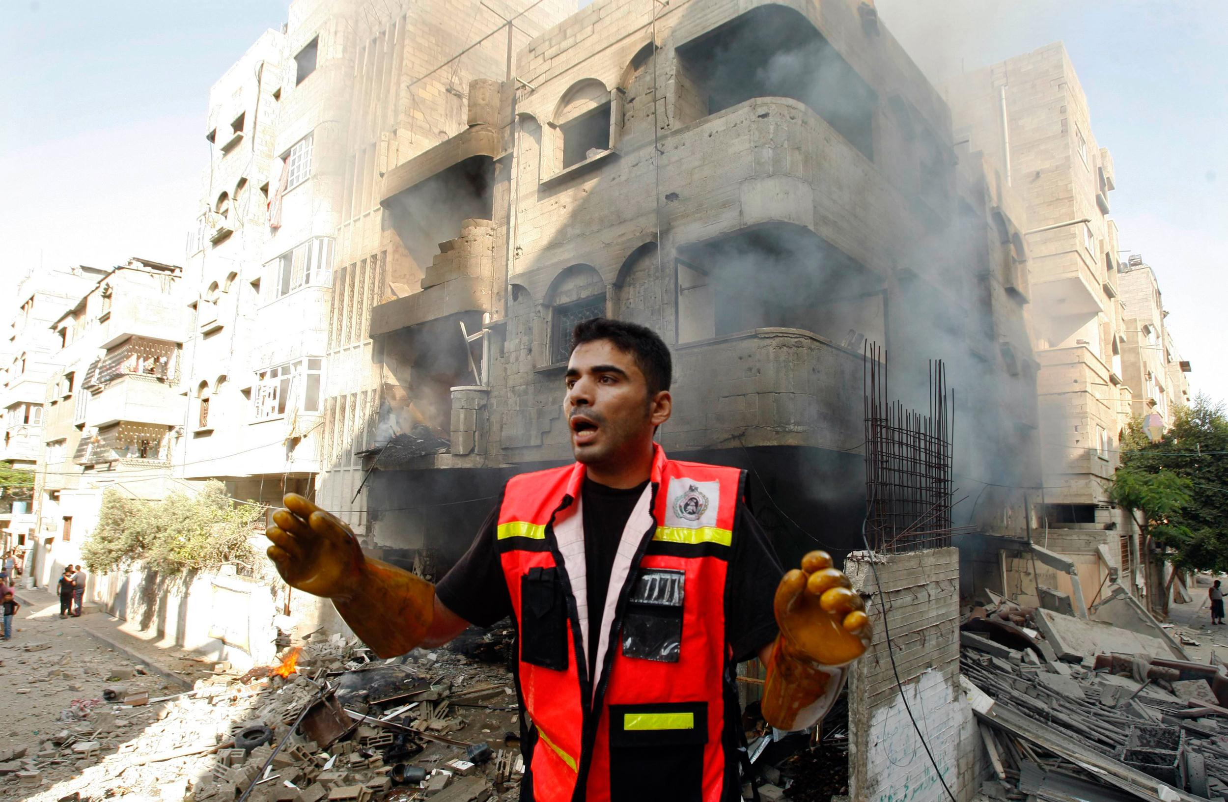 Image: Member of the civil defence reacts after what police said was an Israeli air strike on a house, in Gaza City