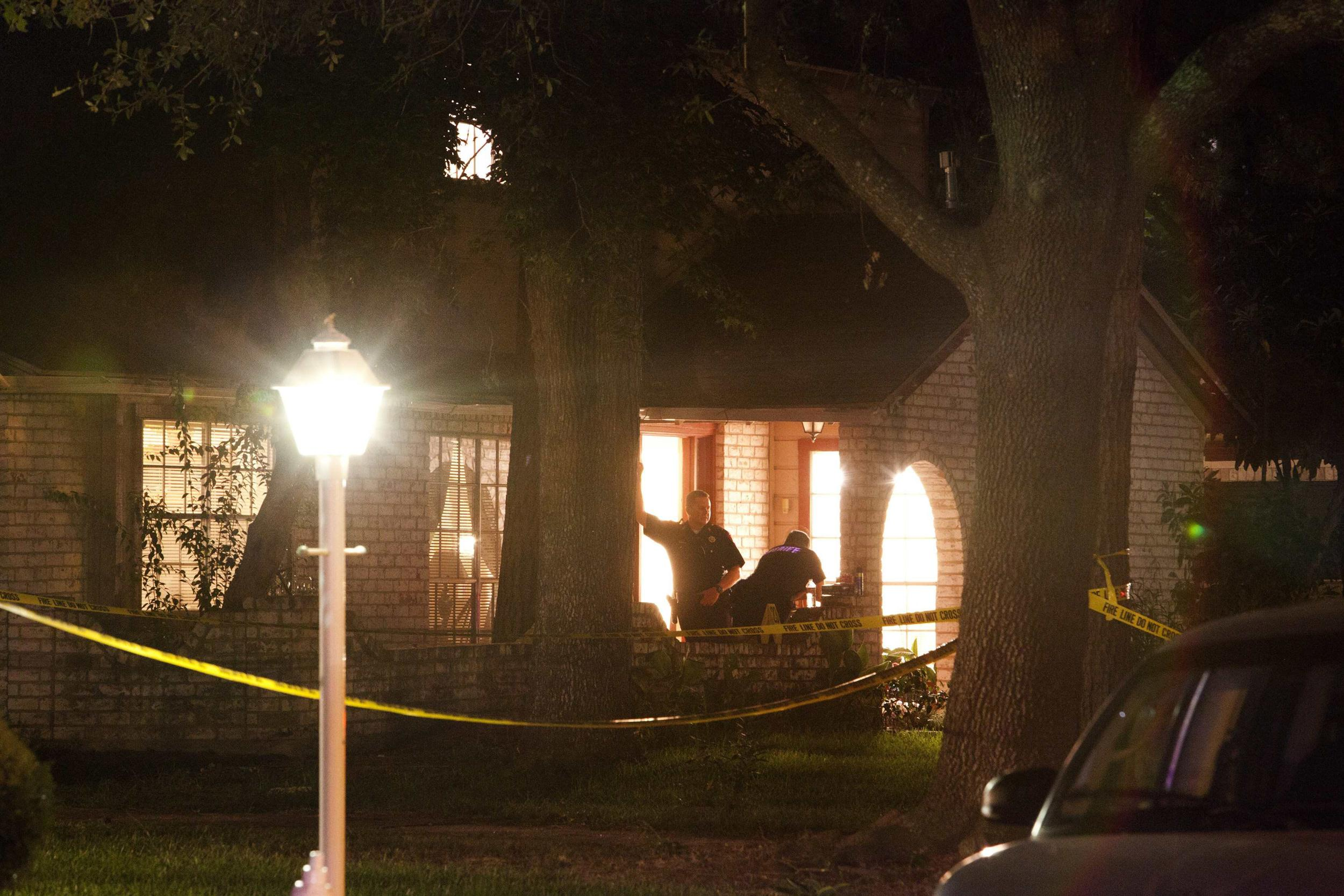 Image: Harris County Precinct 4 constables stand at the door of a home where several people were shot to death, in the Houston suburb of Spring, Texas