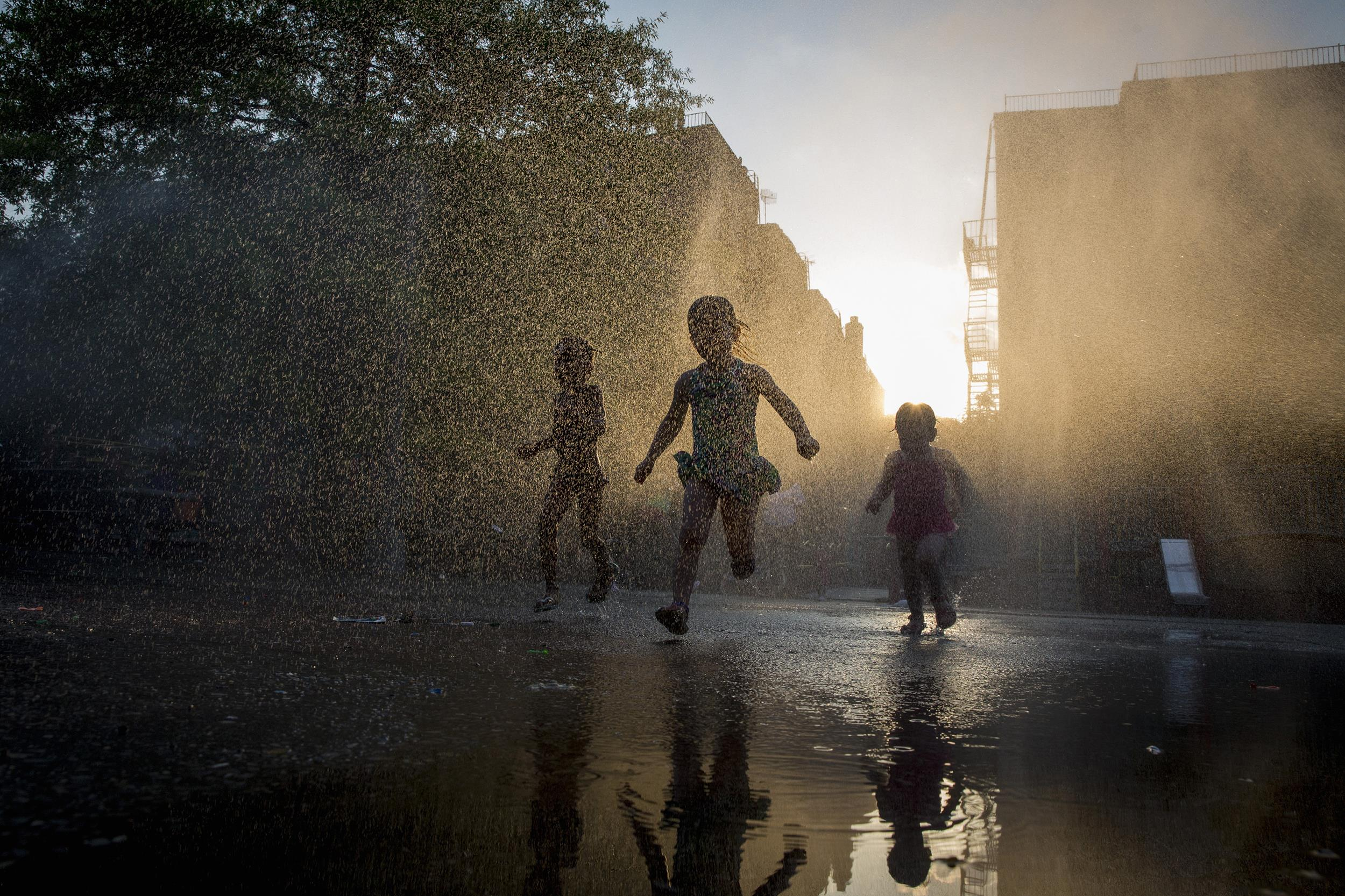 Image: Children play with a sprinkler at a playground in the Park Slope section of the Brooklyn borough of New York
