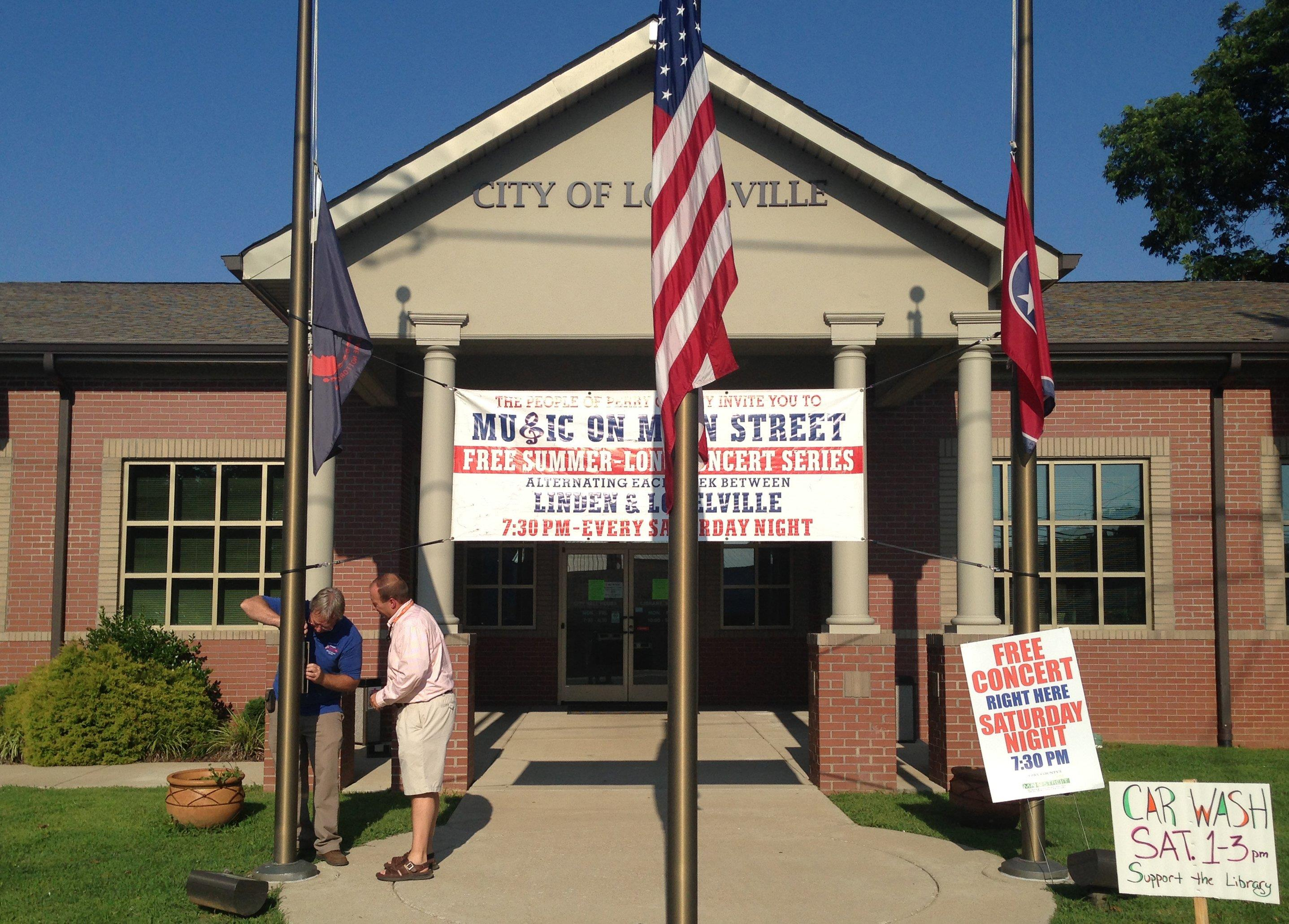 Image: Lobelville Mayor Robby J. Moore, right, and business owner Robert Mathis lower flags in front of City Hall in Lobelville, Tenn.