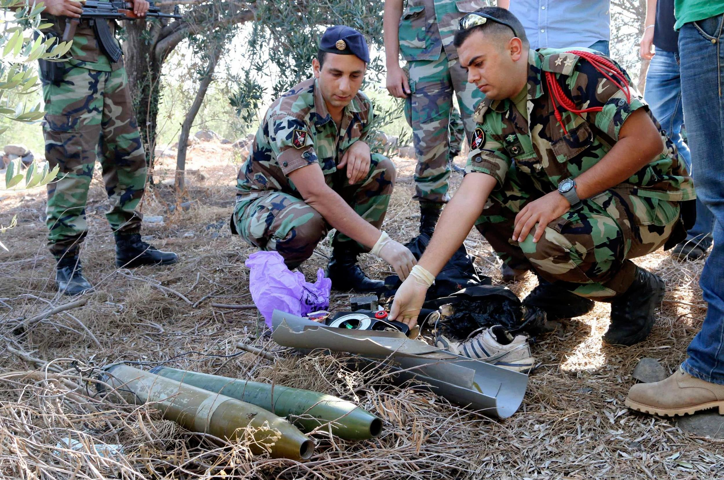 Image: Lebanese army personnel inspect the remains of a shell that was suspected of having been launched from Lebanon to Israel, near the village of El Mari in Southern Lebanon