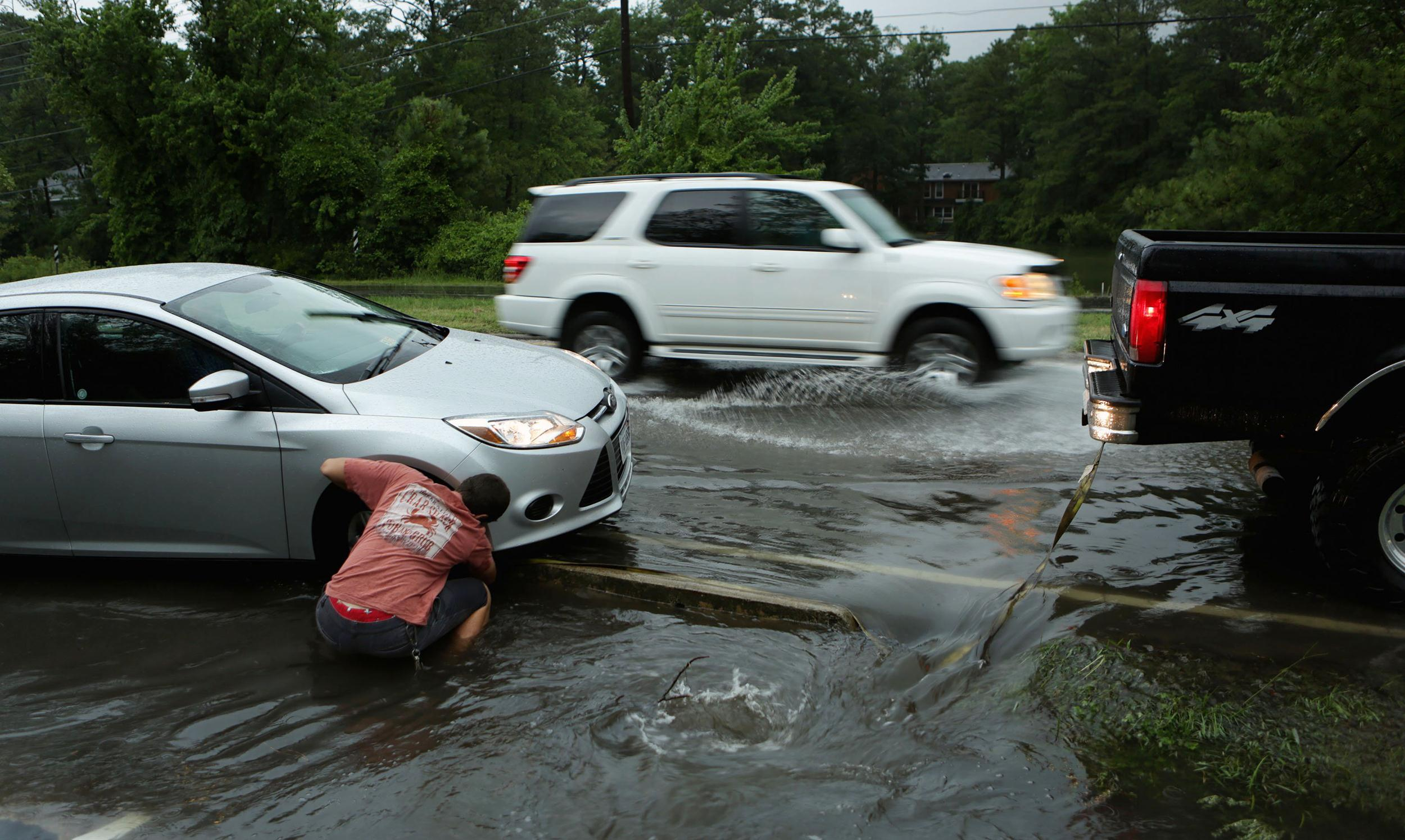 Image: Garrison Crigger fastens a tow rope to another motorist's stuck car during a rush-hour thunderstorm in Virginia Beach