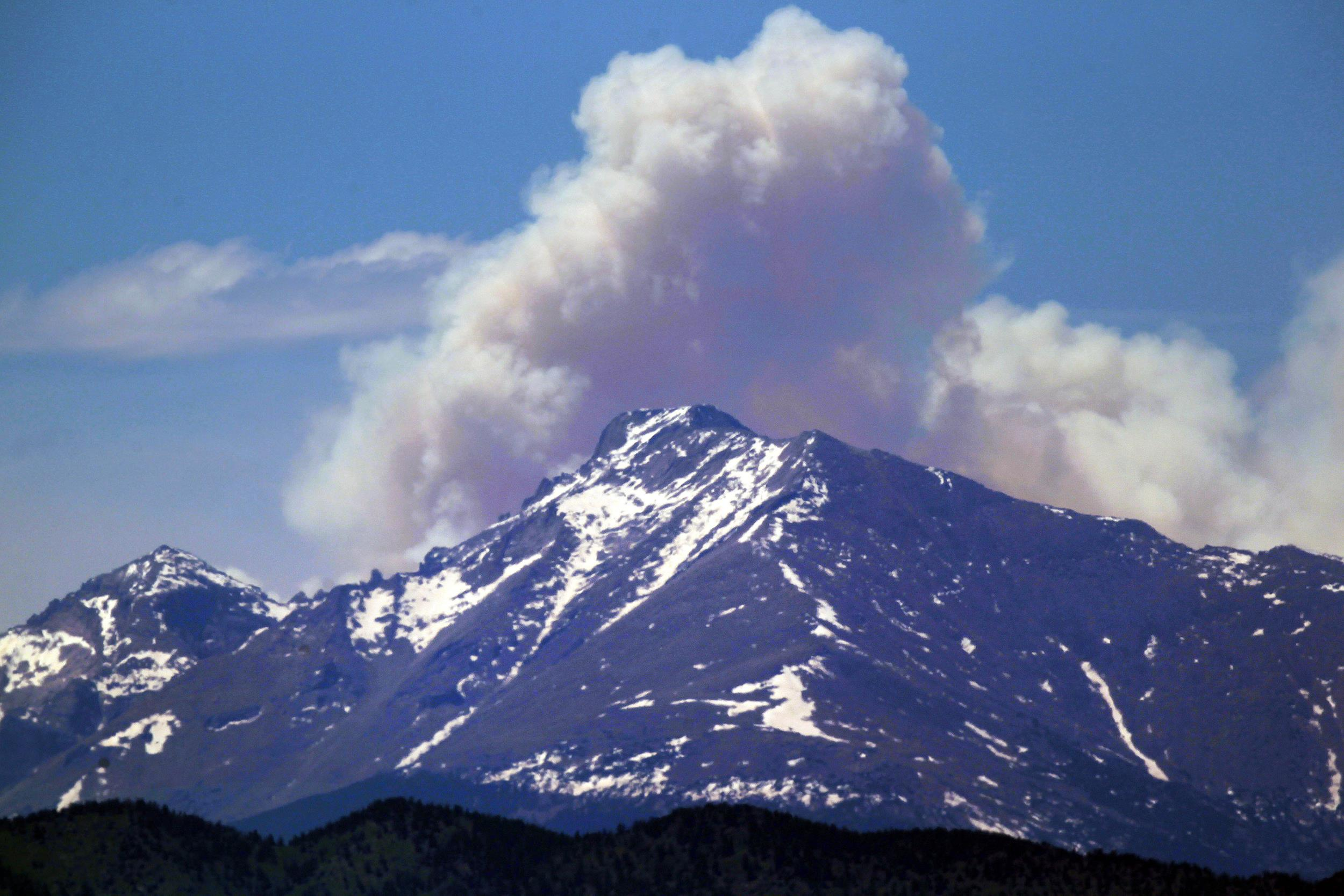 Image: A plume of smoke from the Big Meadows Fire in Rocky Mountain National Park rises above Longs Peak, as seen from just east of Boulder, Colo., on June 11