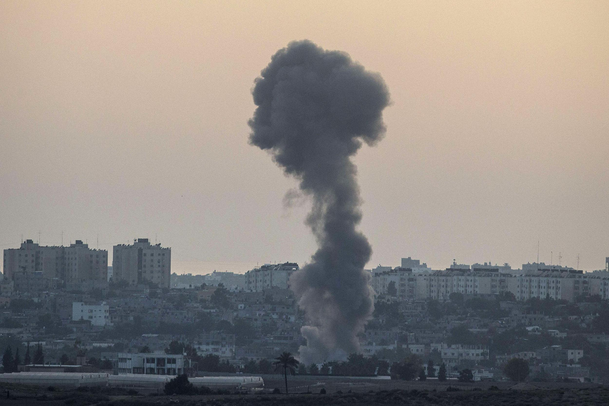 Image: Smoke billowing from buildings following an Israeli air strike in Gaza City