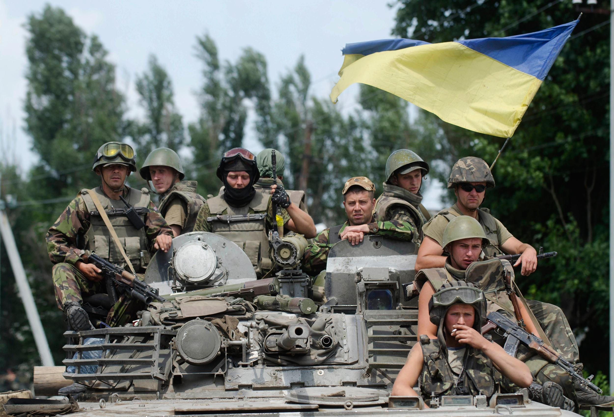 Image: Ukrainian government soldiers sit atop an armored personal carrier