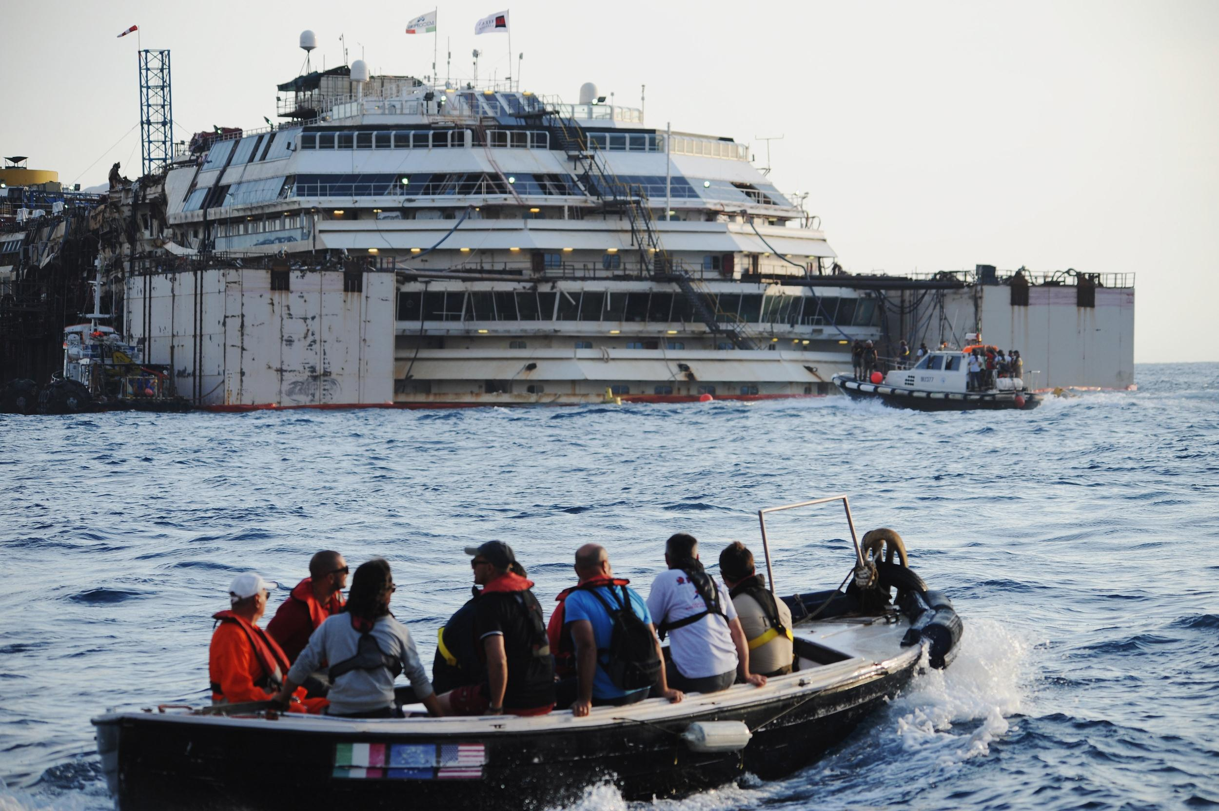 Image: Titan-Micoperi workers make their way out to the wrecked ship Costa Concordia before the start of the refloating operations