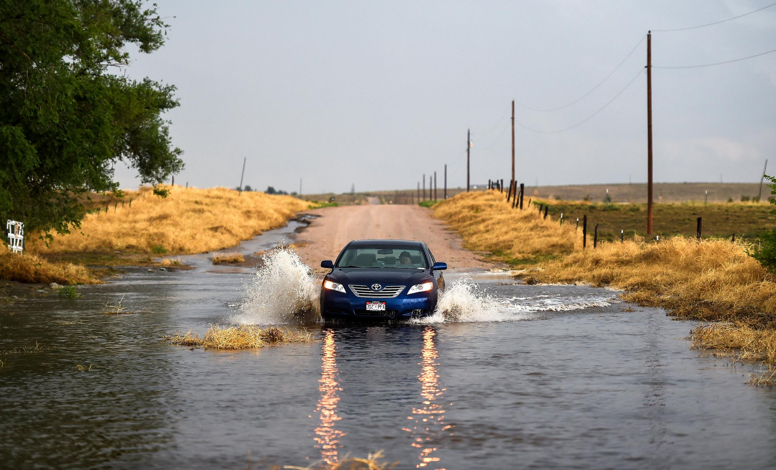 Image: A car enters a flooded portion a road following a storm