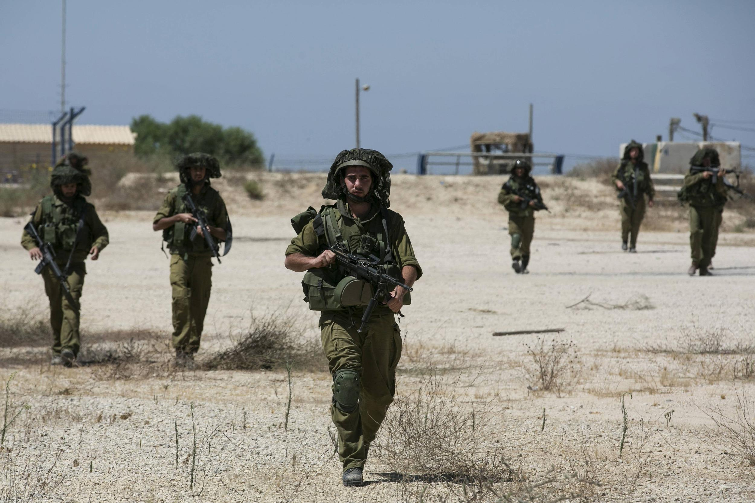 Image: Israeli soldiers walk near the border with the Gaza Strip
