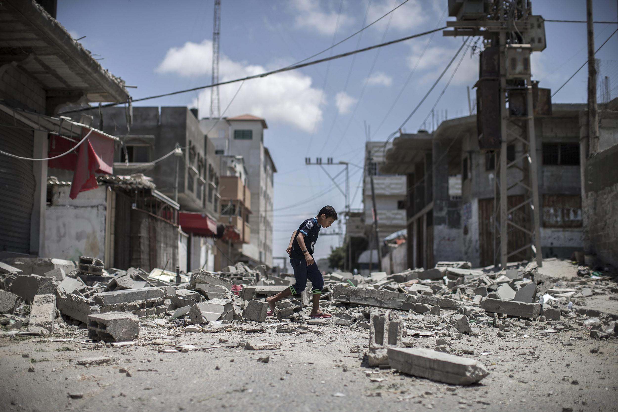 Image: A young Palestinian boy walks over debris from a house that was destroyed overnight in an airstrike in Deir Al Balah, central Gaza Strip, on July 14