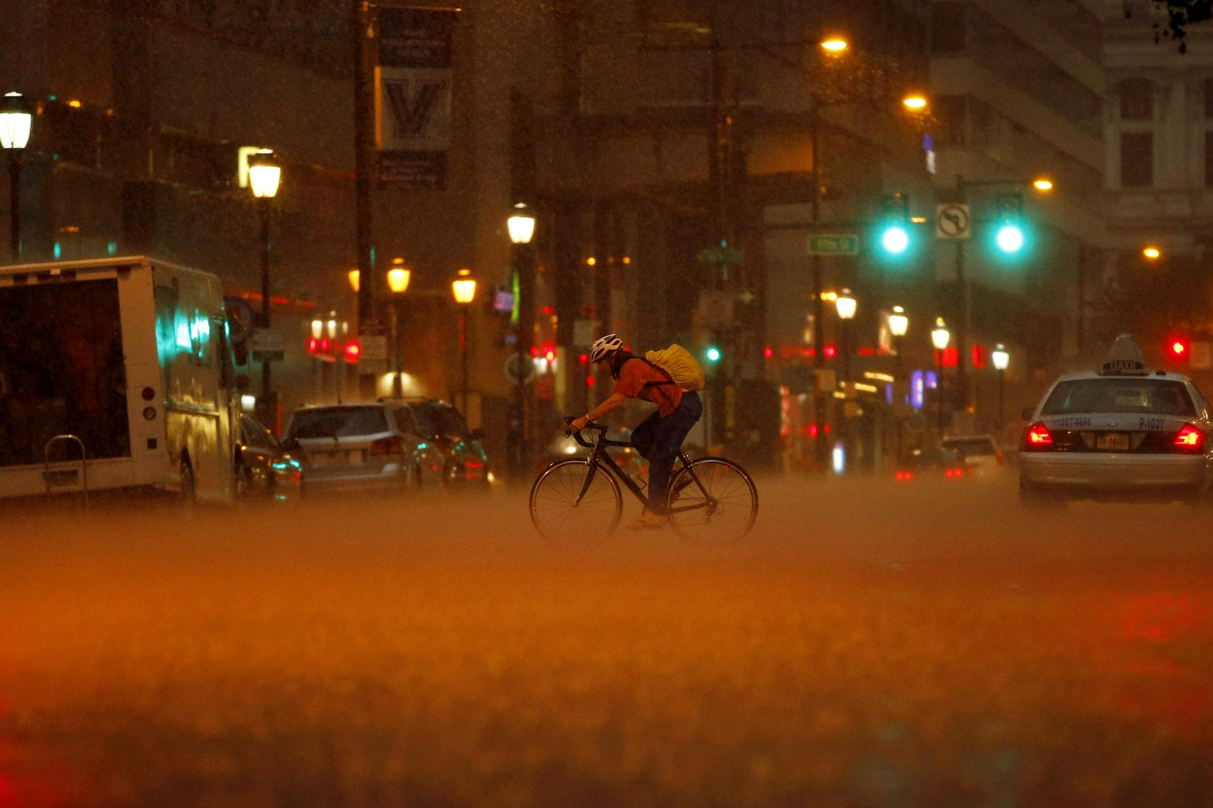 Image: A woman pedals her bike through a heavy rain storm, on July 14 in Philadelphia.