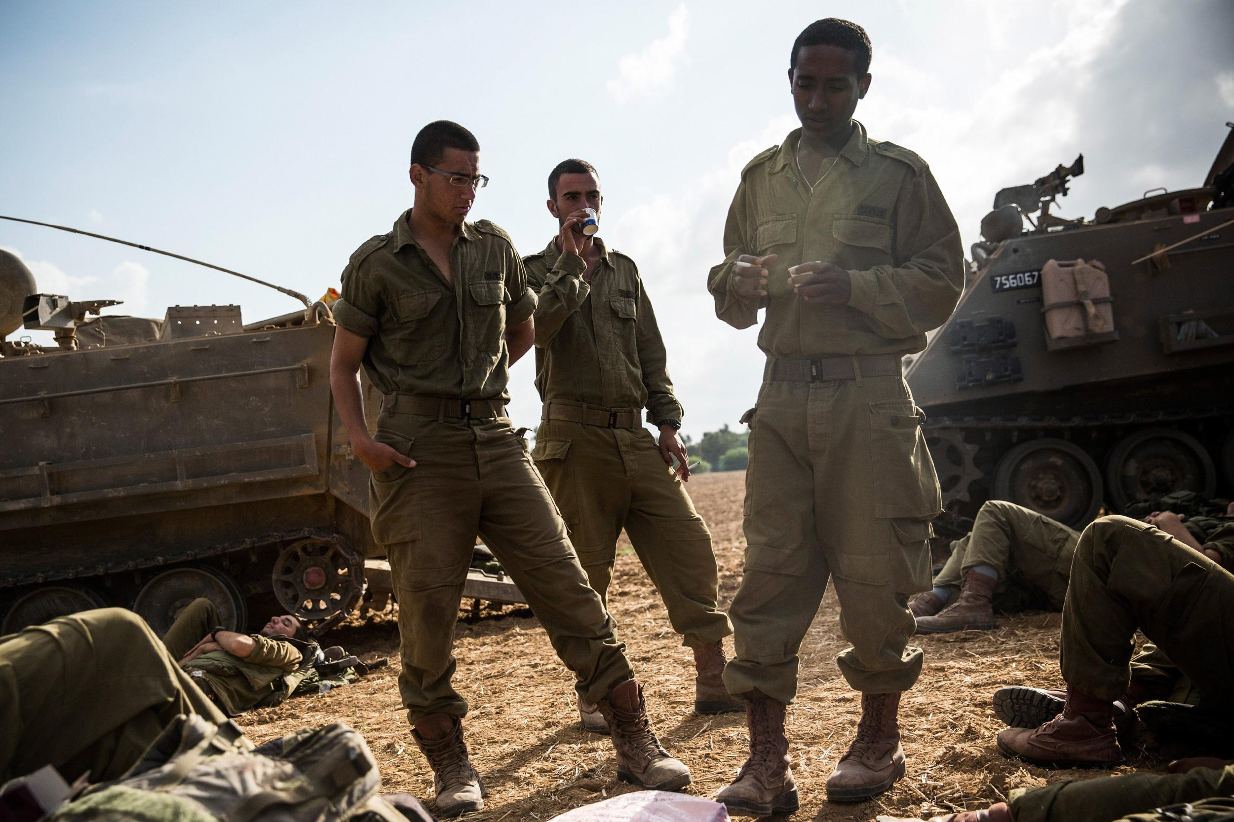 Image: Israeli soldiers wake up after sleeping next to armored personnel carriers near the Israeli-Gaza border