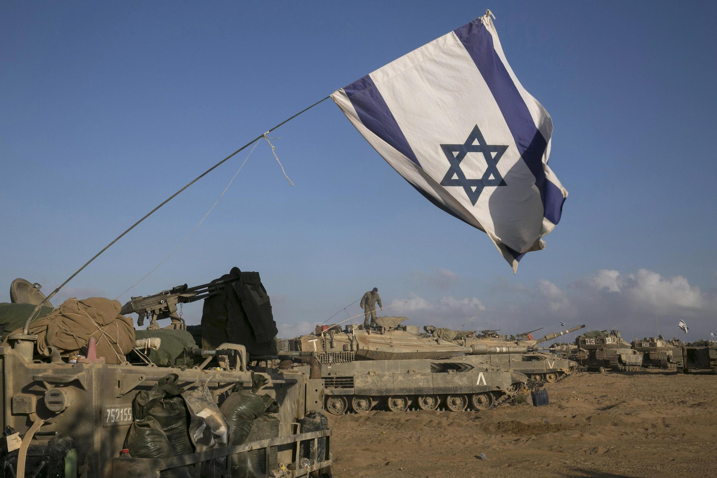 Image: Israeli tanks and armoured personnel carriers are seen at a staging area outside the central Gaza Strip