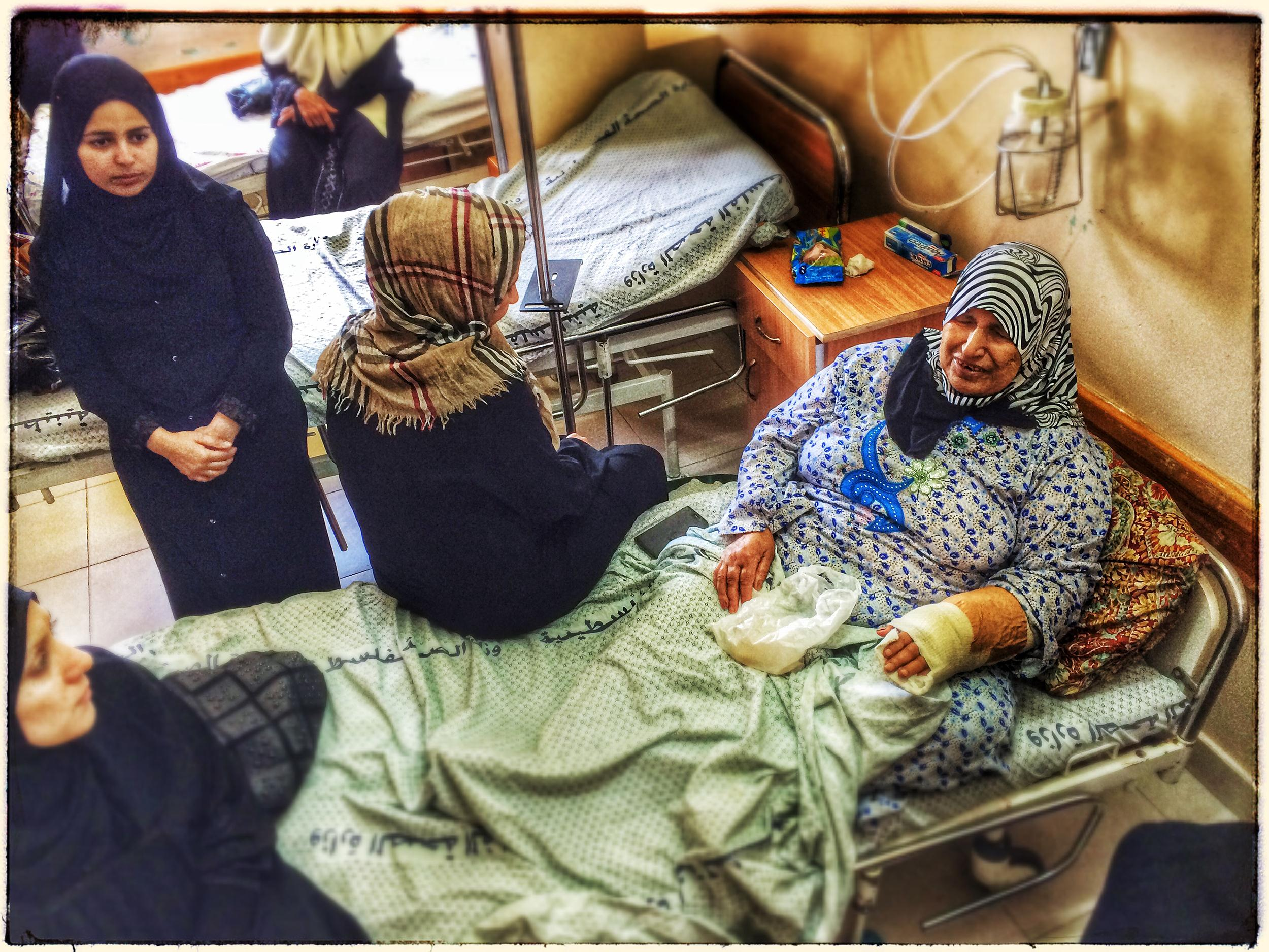 Image: Na'ema Al Battch, the grandmother of the Al Battch family, being comforted by other women at Gaza'a Shifa Hospital.