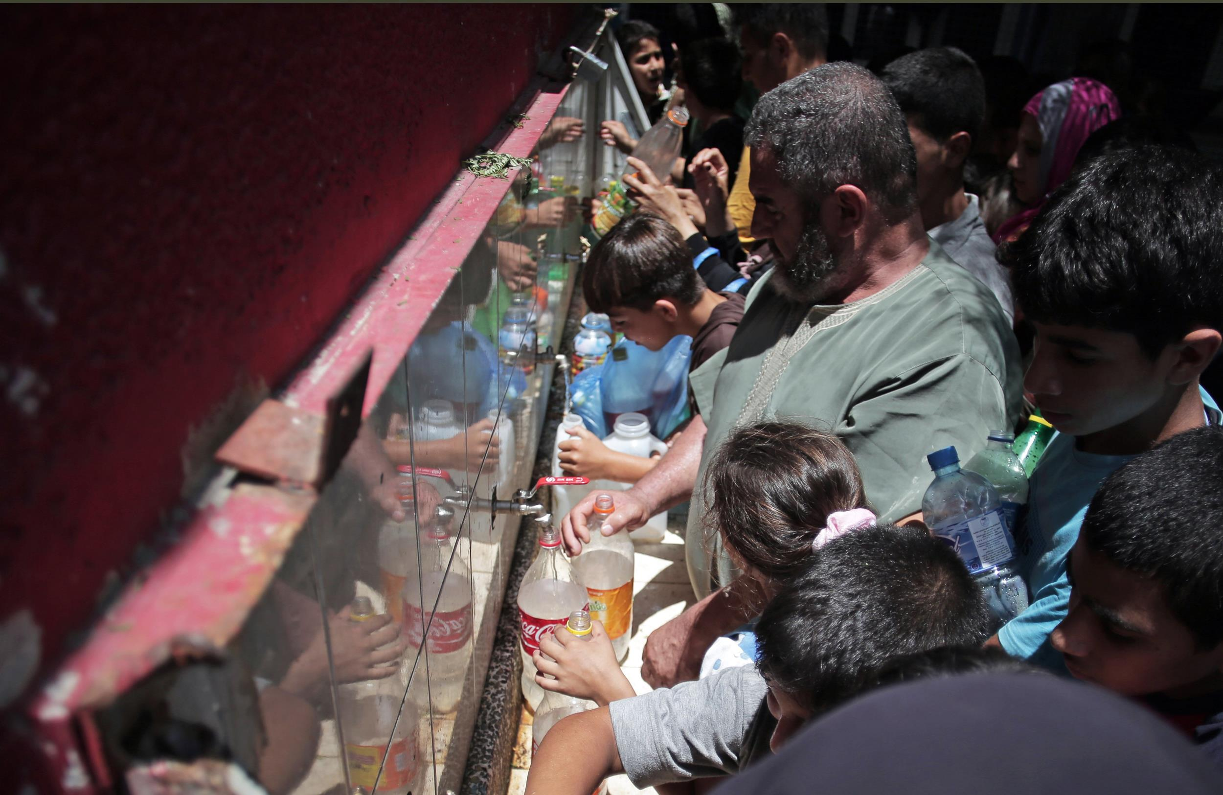 Image: Displaced Palestinians fill empty bottles of water at the New Gaza Boys United Nations School