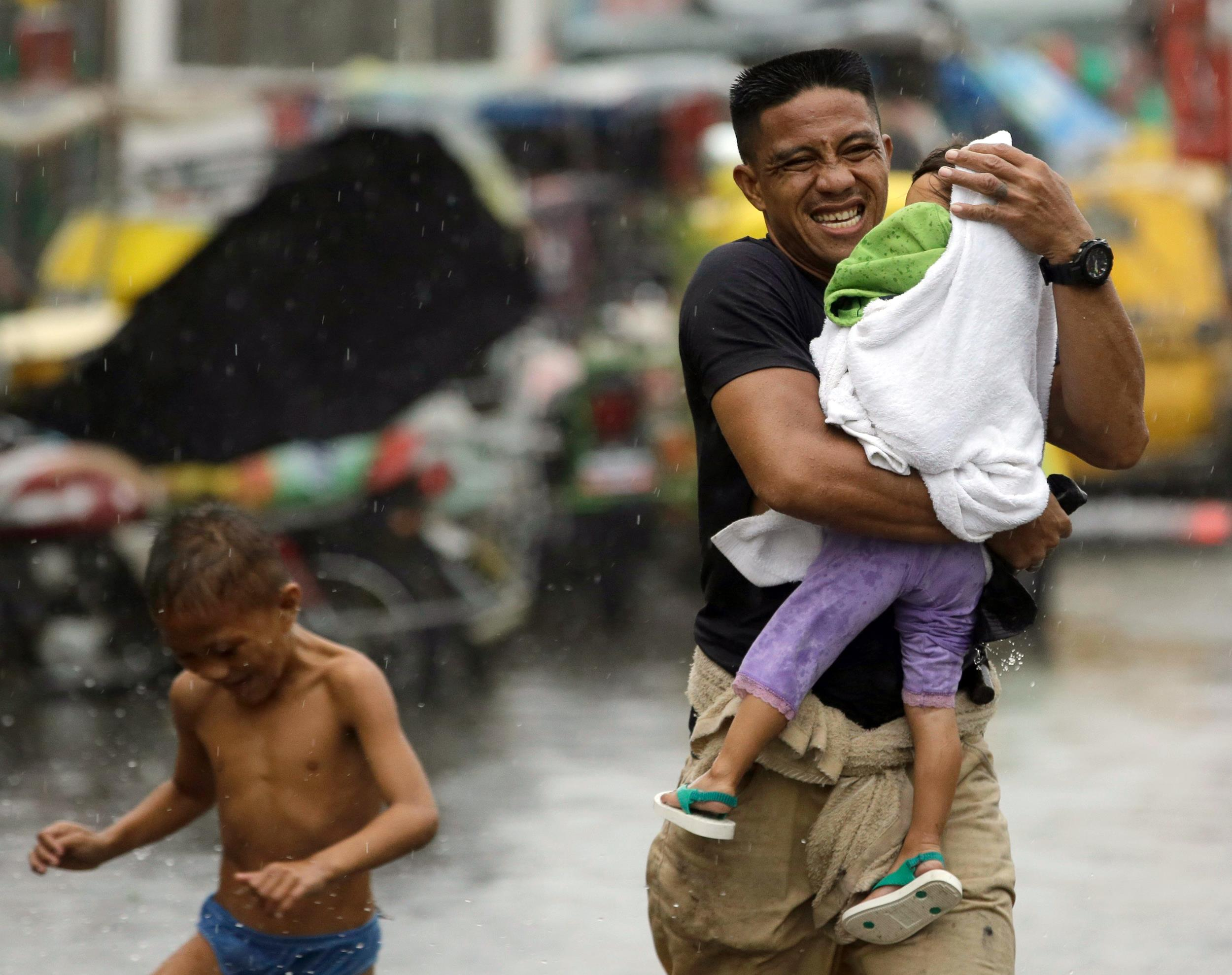 Image: Residents at the slum community of Baseco evacuate to safer grounds during the onslaught of Typhoon Rammasun
