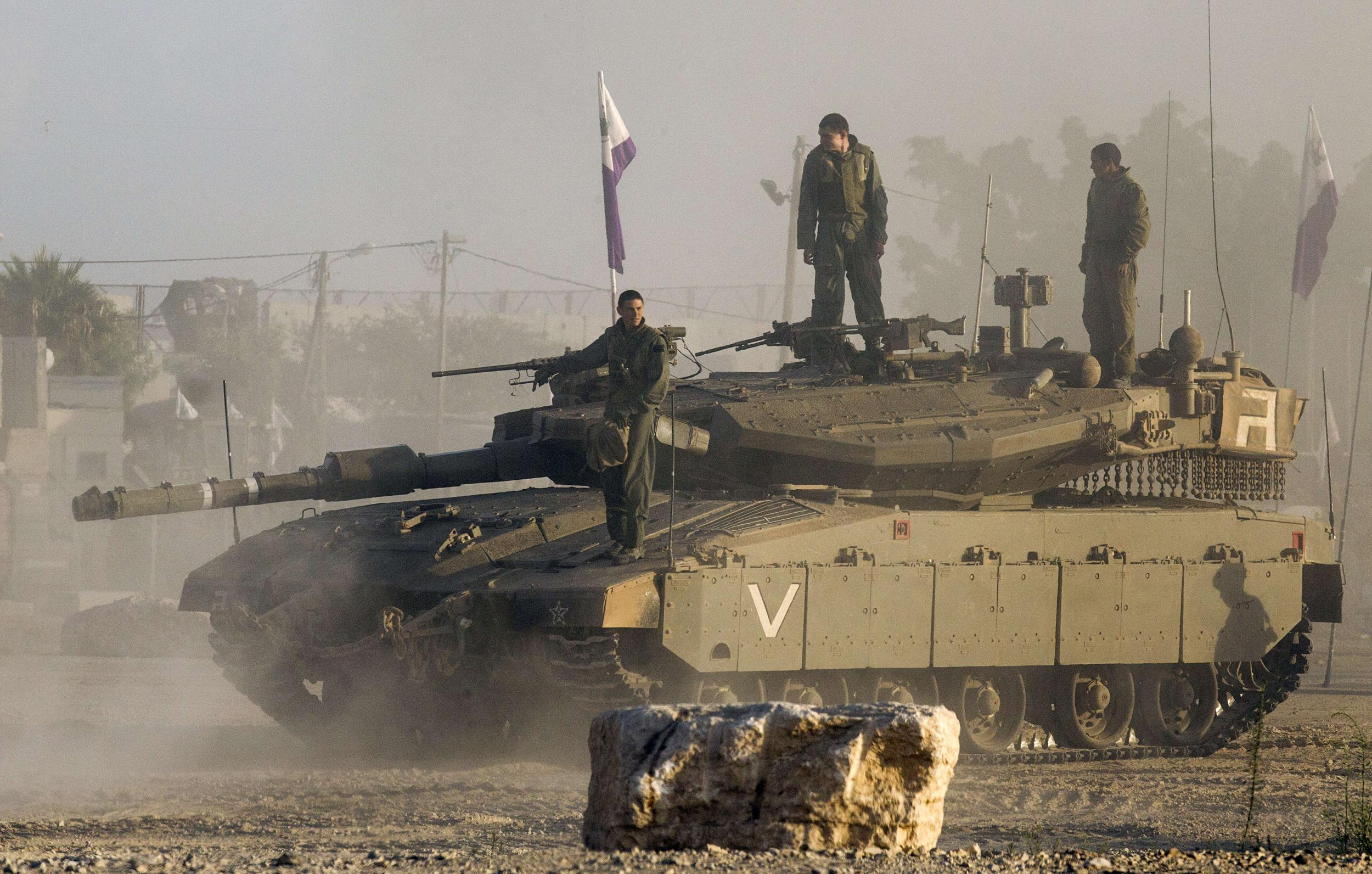 Image: Israeli soldiers stand on their Merkava tank on July 17, 2014 at an army deployment area near Israel's border with the Gaza Strip