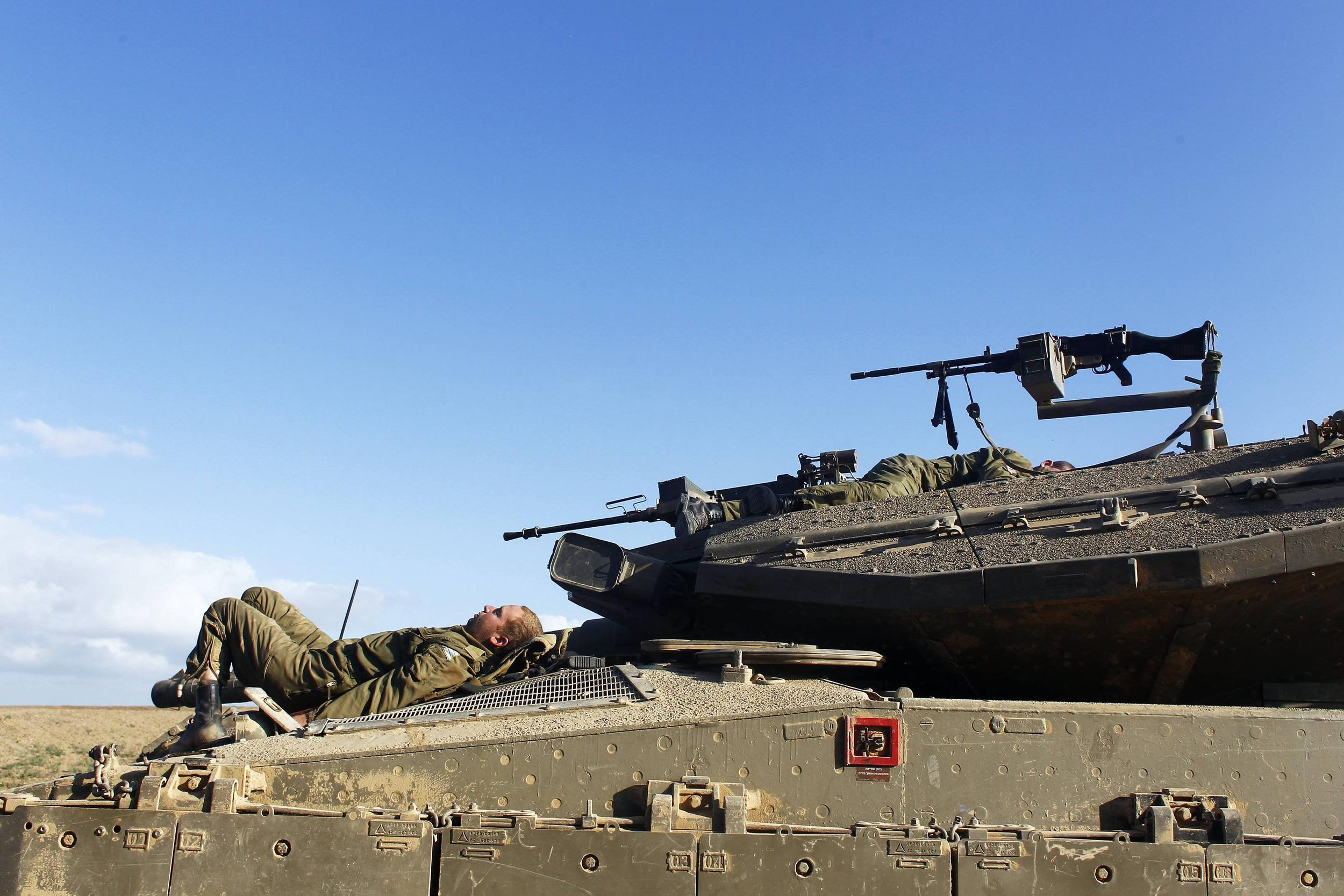 Image: Israeli soldiers rest atop tanks outside the central Gaza Strip