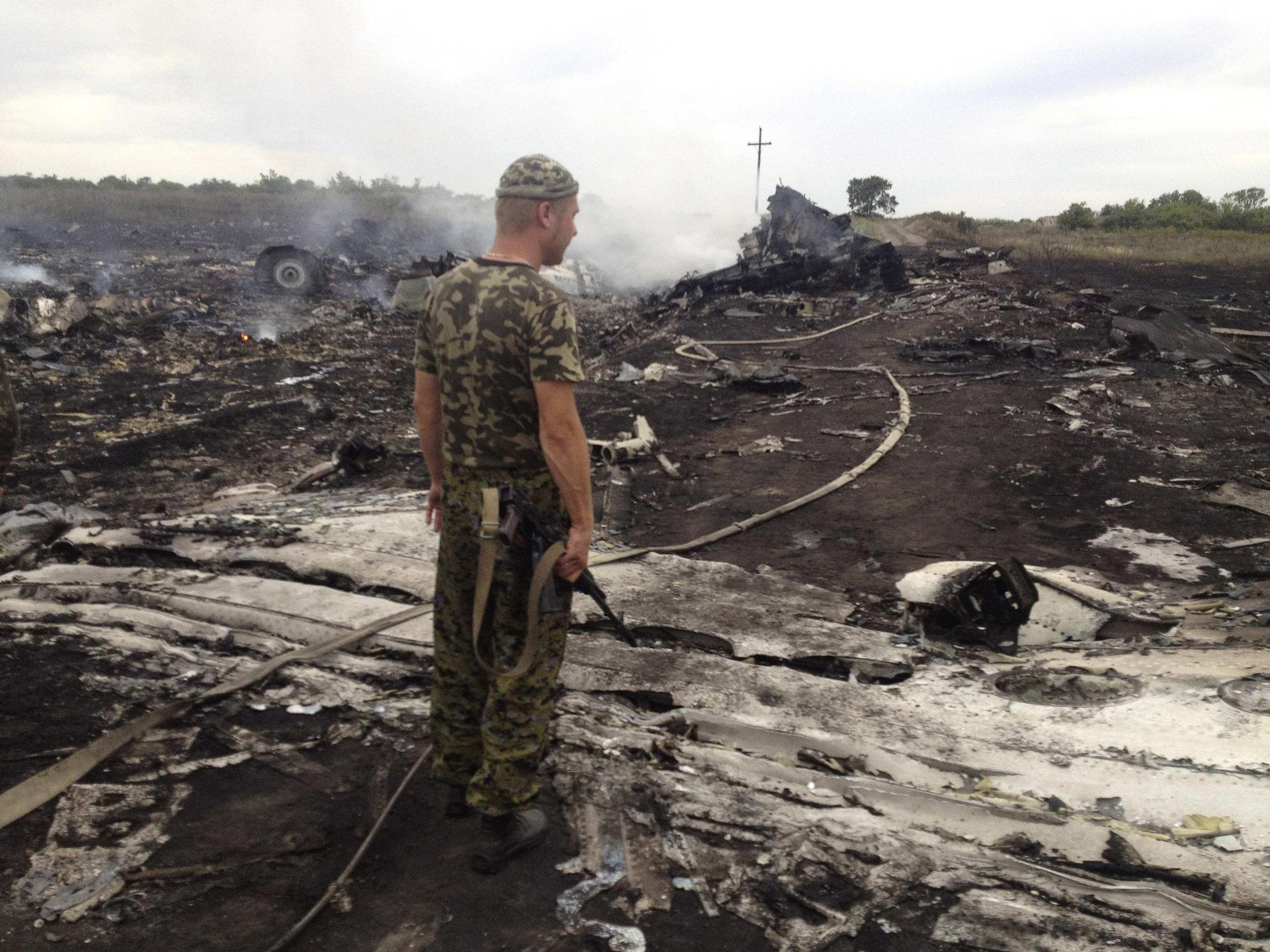 Image: Armed pro-Russian separatist stands at a site of a Malaysia Airlines Boeing 777 plane crash in the settlement of Grabovo in the Donetsk region