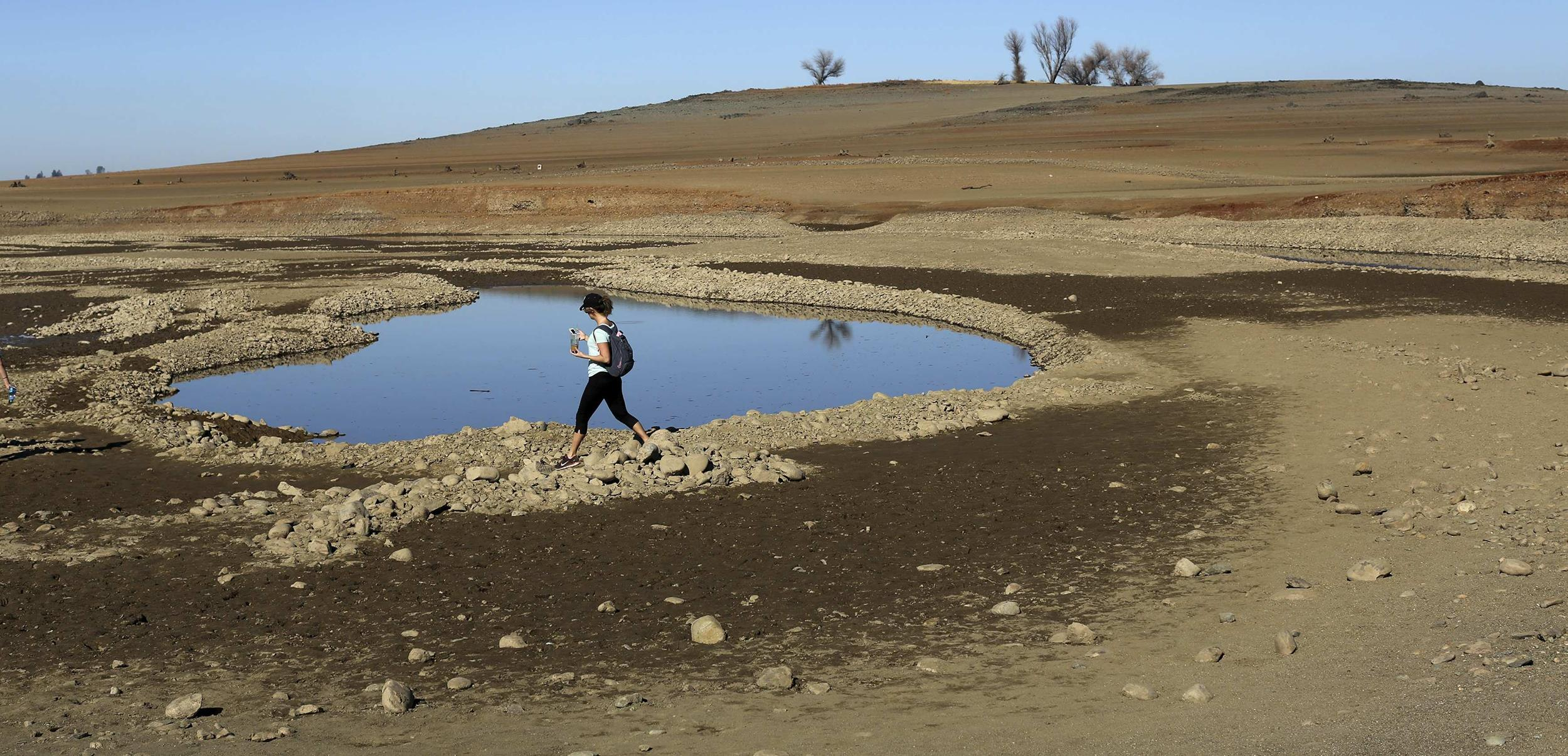 Image: File photo of a visitor walking near the receding waters at Folsom Lake, which is 17 percent of its capacity, in Folsom