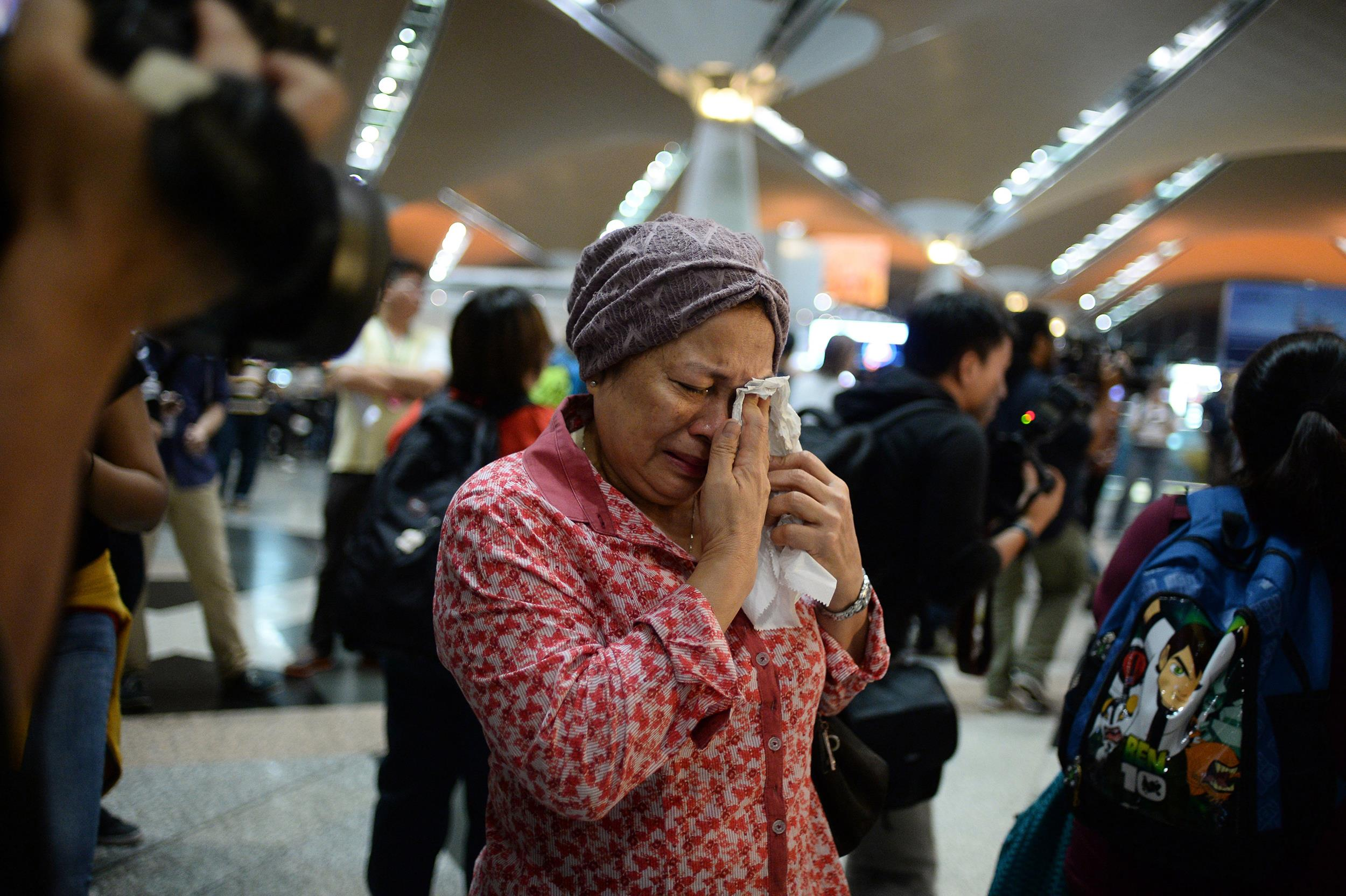 Image: A woman reacts to news regarding a Malaysia Airlines plane that crashed in eastern Ukraine at Kuala Lumpur International Airport in Sepang, Malaysia, on July 18.