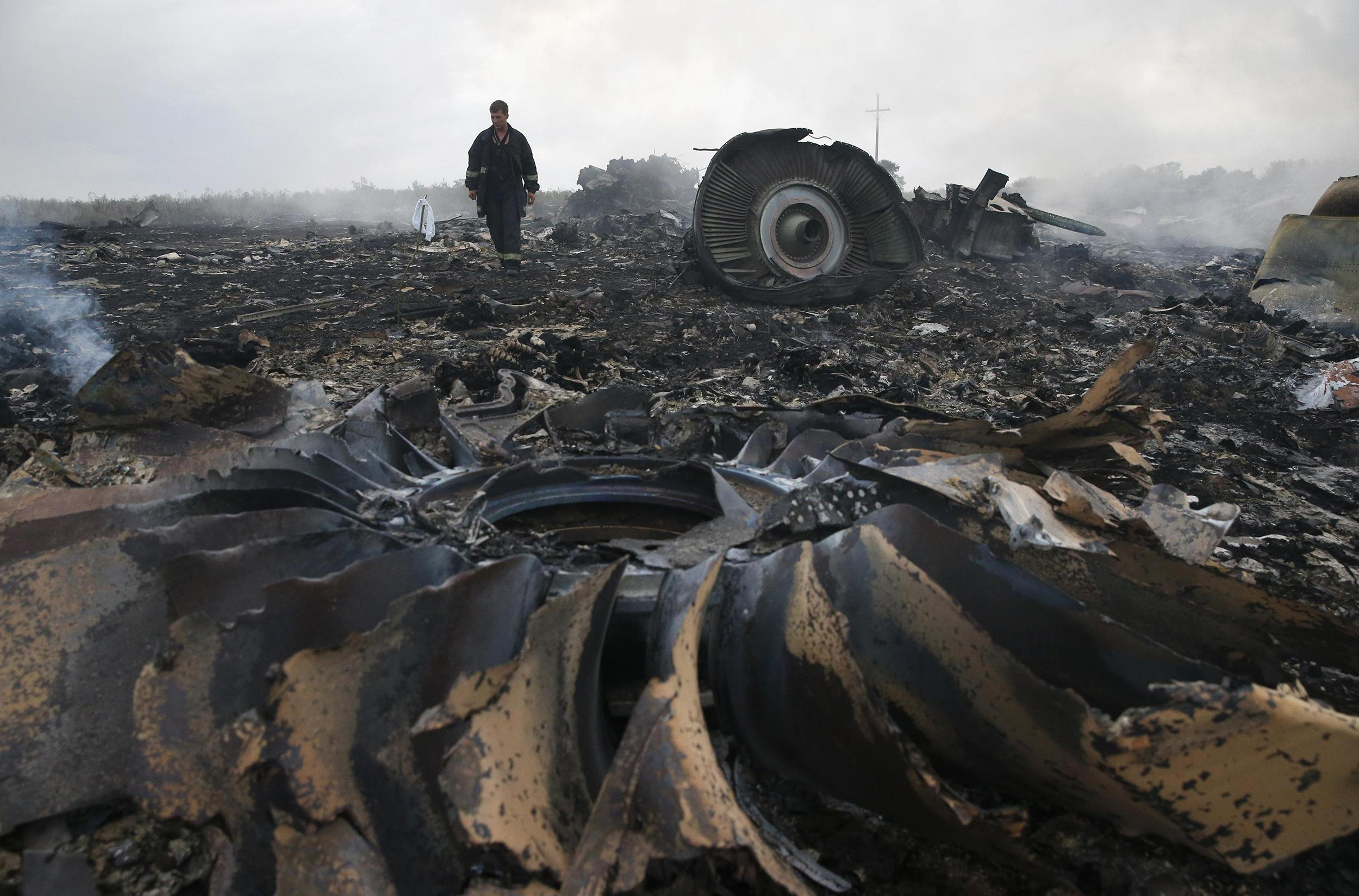 Image: Emergencies Ministry member walks at a site of a Malaysia Airlines Boeing 777 plane crash near the settlement of Grabovo in the Donetsk region