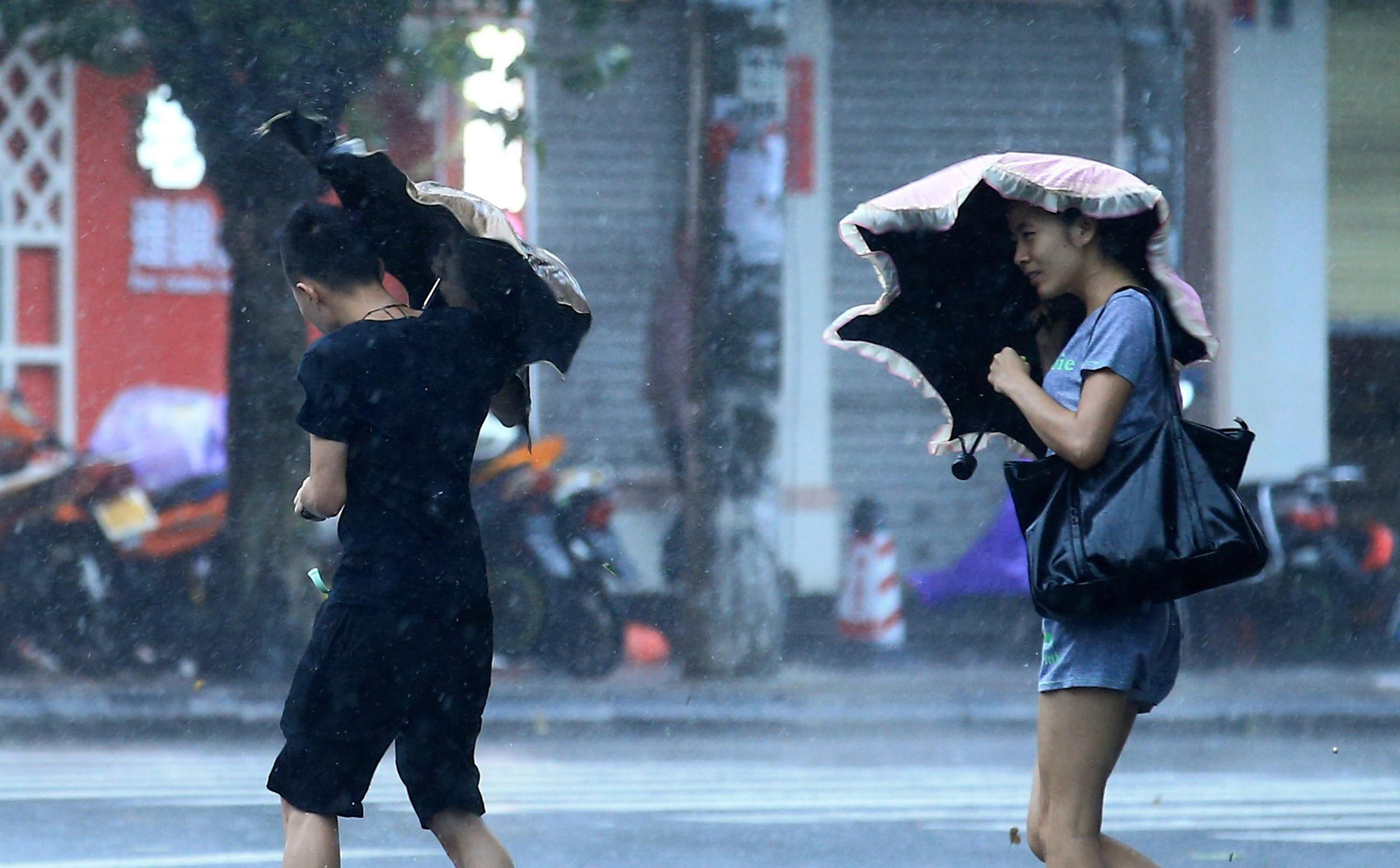 Image: Residents walk on a street in heavy rain and strong wind in Haikou, south China's Hainan province