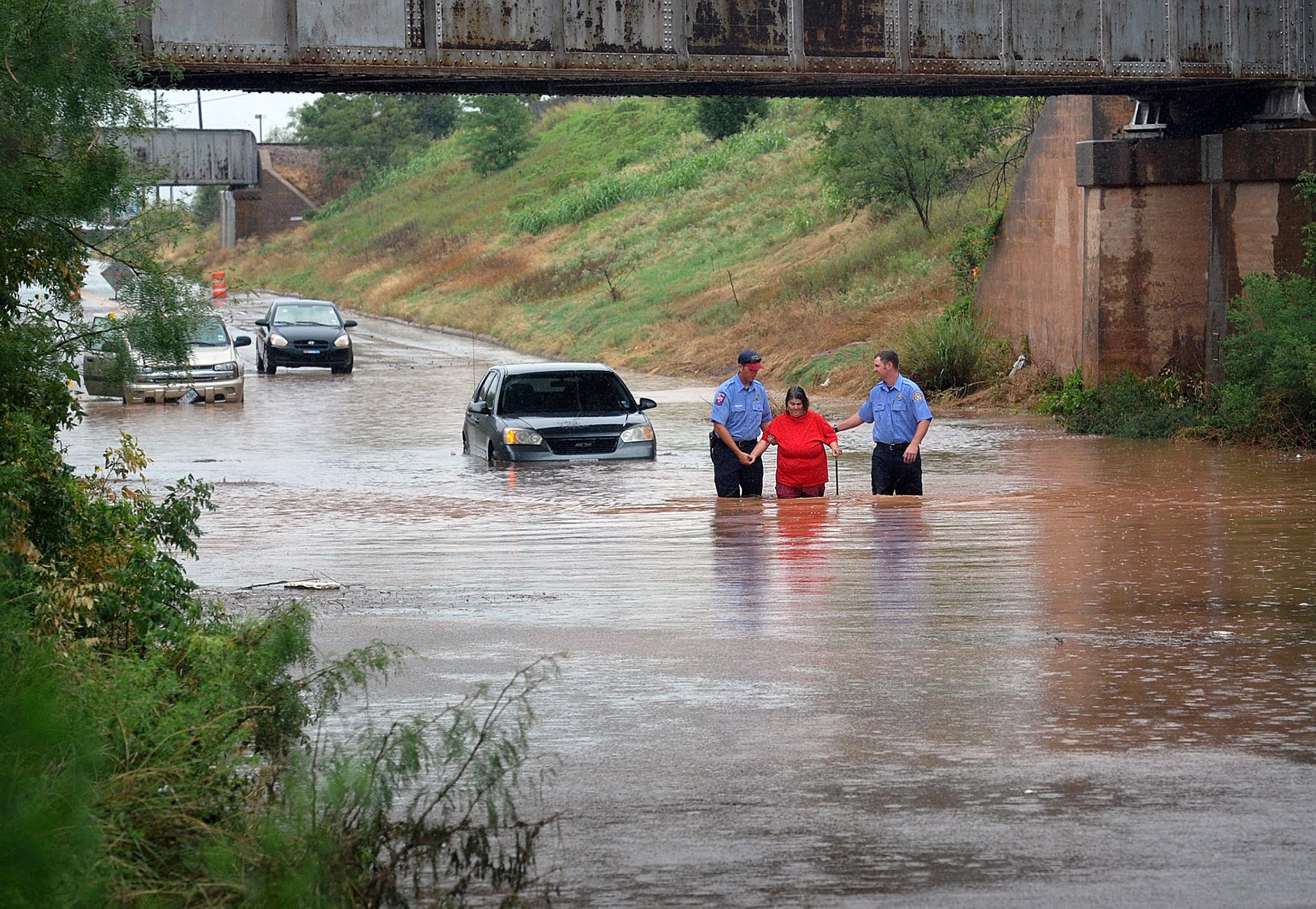 Image: Firefighters rescue a woman Thursday after her car stalled in high water in Wichita Falls, Texas.