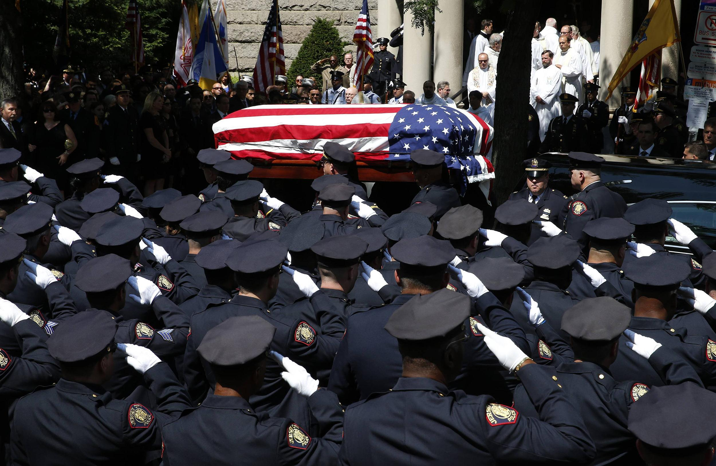 Image: Police officers salute as the casket carrying slain Jersey City police officer Melvin Santiago is carried into St. Aloysius Catholic Church for his funeral service in Jersey City