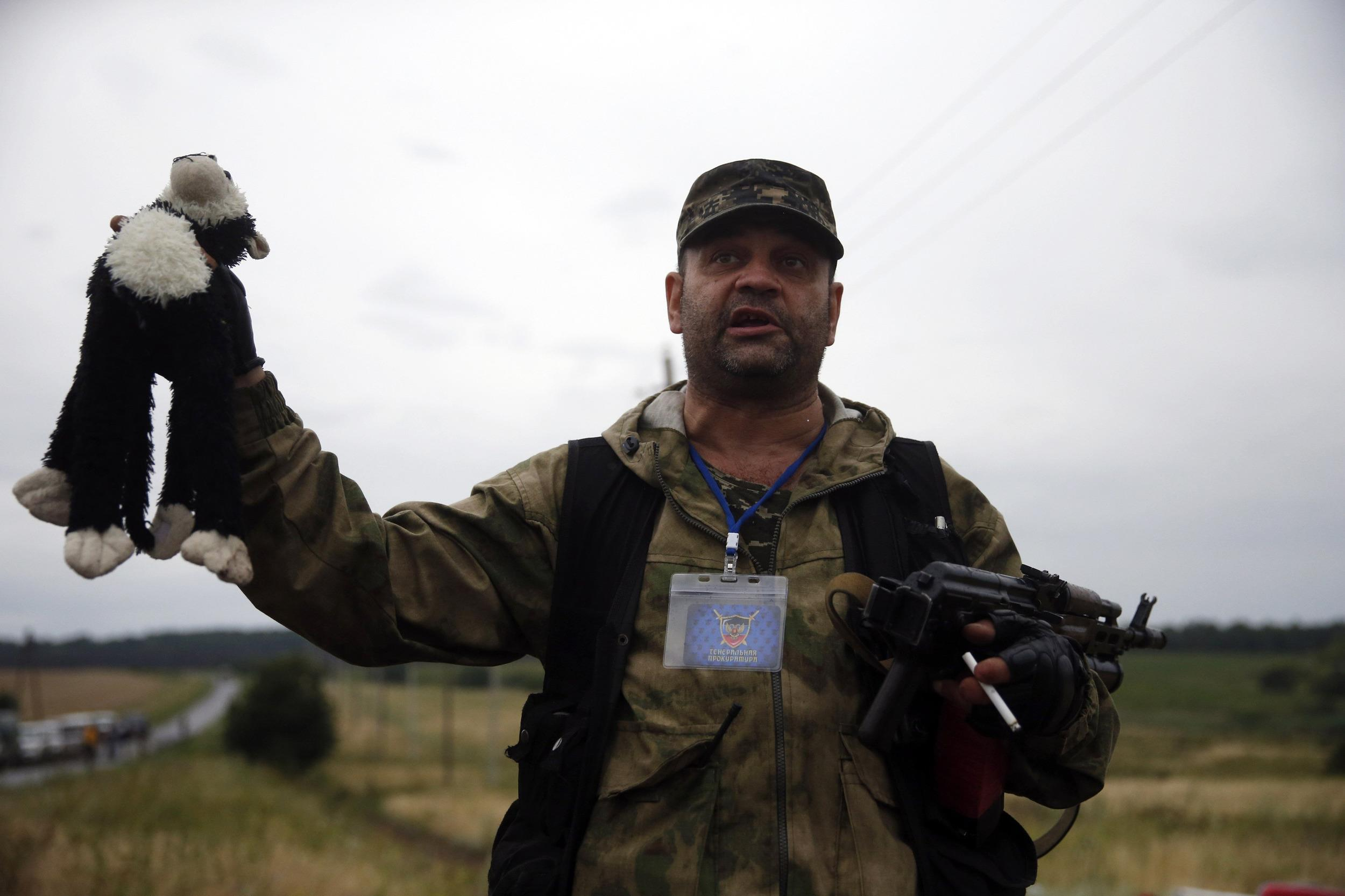 A pro-Russian separatist holds up a stuffed toy found at the crash site of Malaysia Airlines flight MH17, near the settlement of Grabovo in the Donetsk region