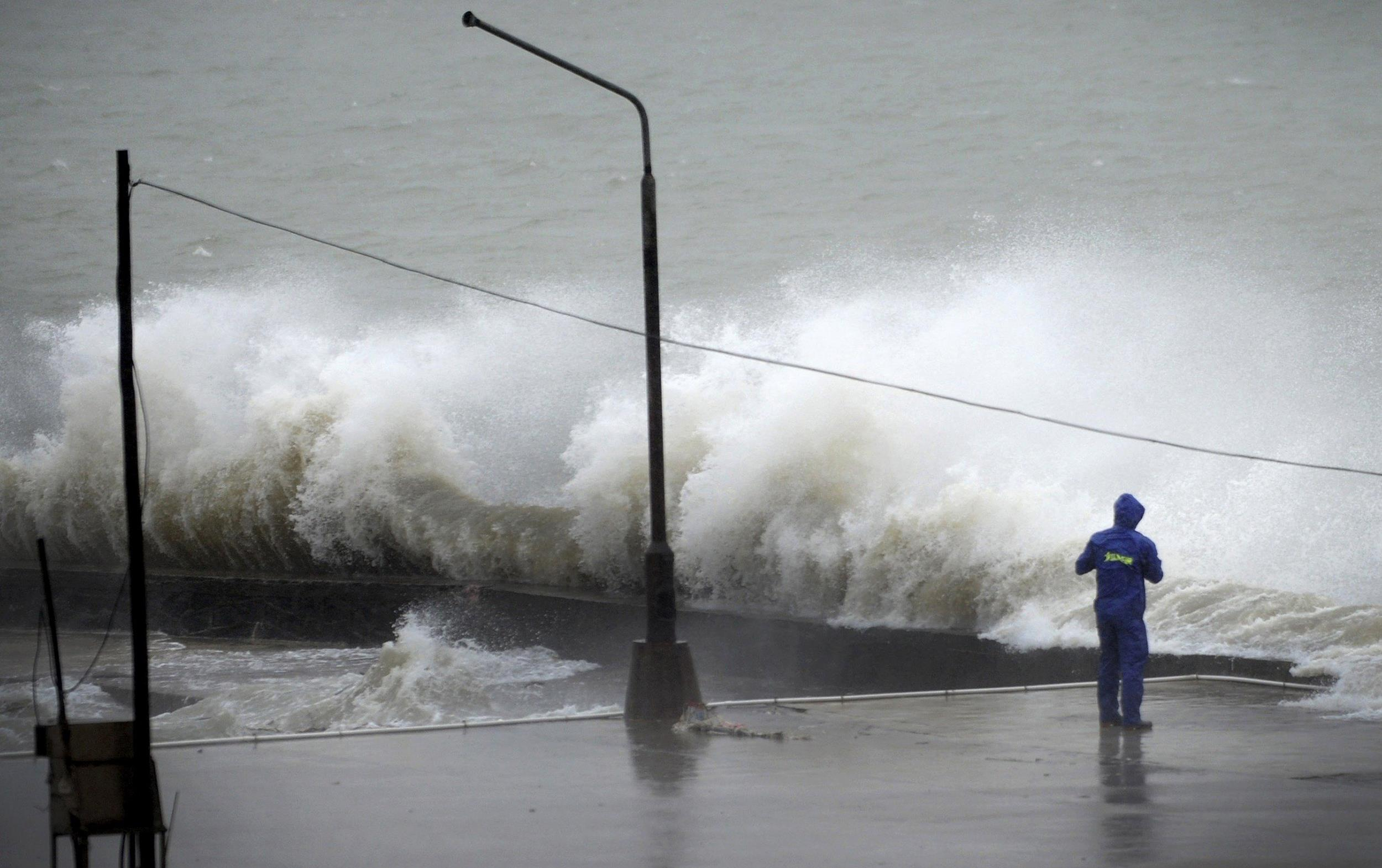 Image: A man looks on as a wave surges under the influence of Typhoon Rammasun at a port in Zhanjiang, Guangdong province