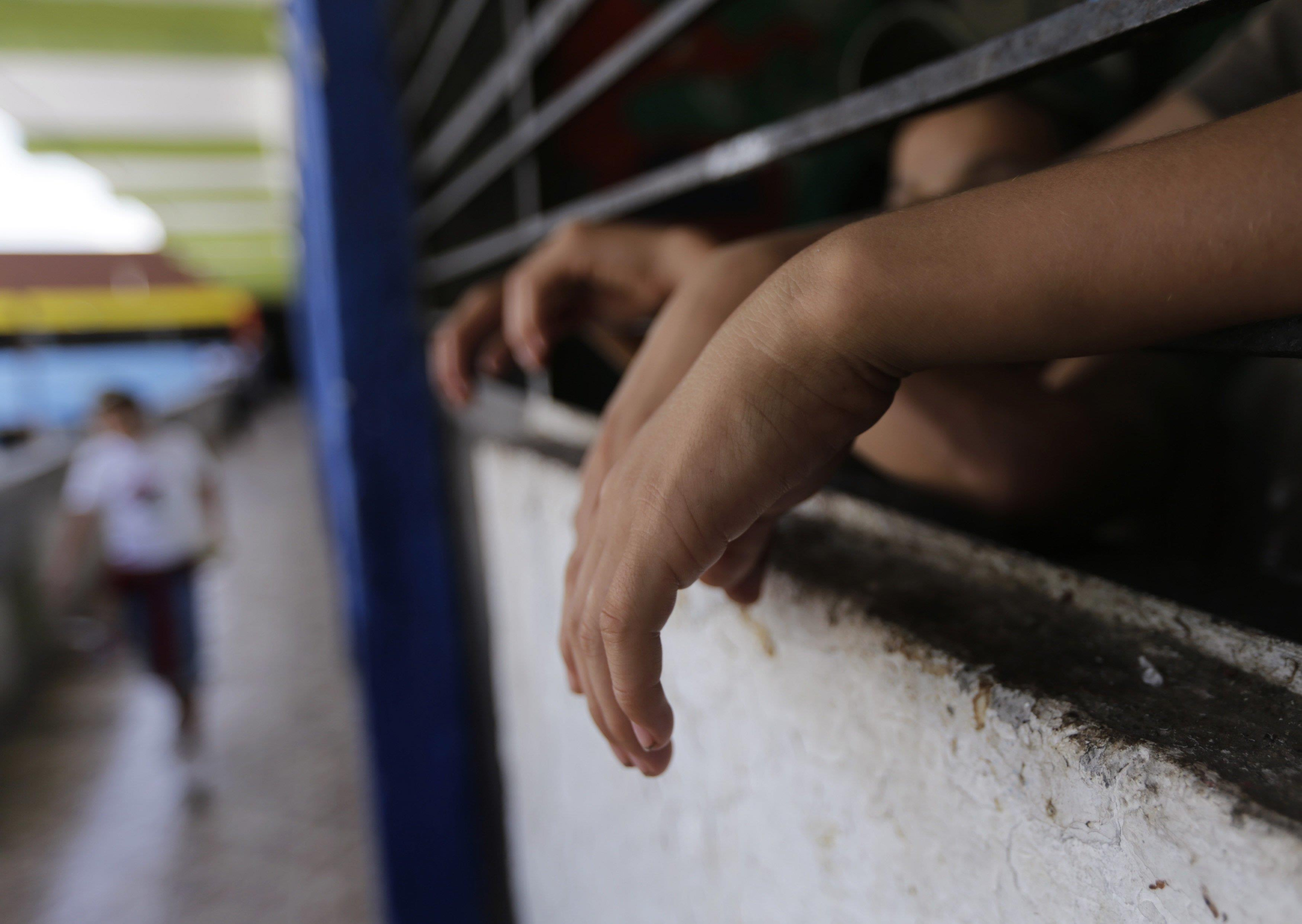 Image: Children place their hands on a barred window inside a home known as