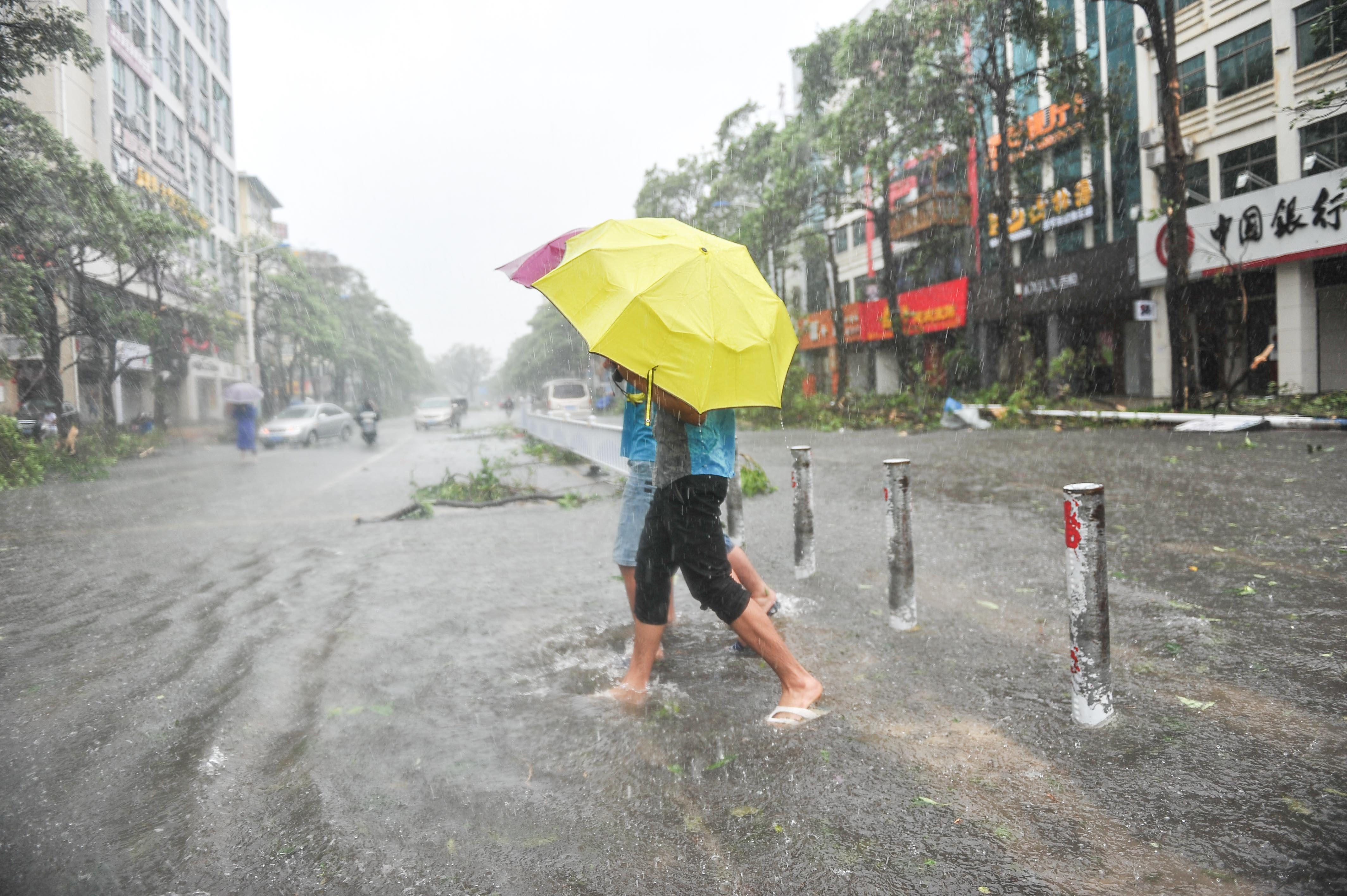 Image: Residents walk on a street as typhoon Rammasun brings torrential rains