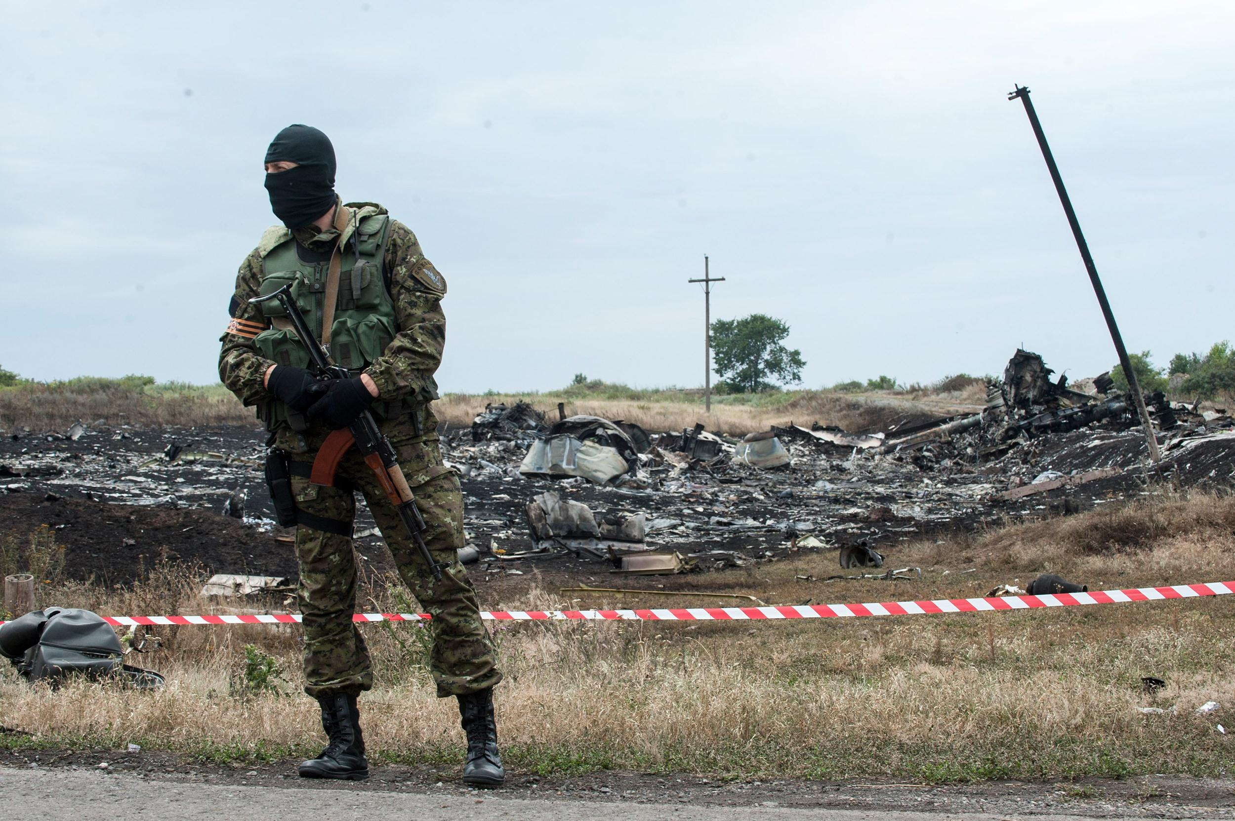 Image: A pro-Russian fighter guards the crash site of a Malaysia Airlines jet near the village of Hrabove, eastern Ukraine