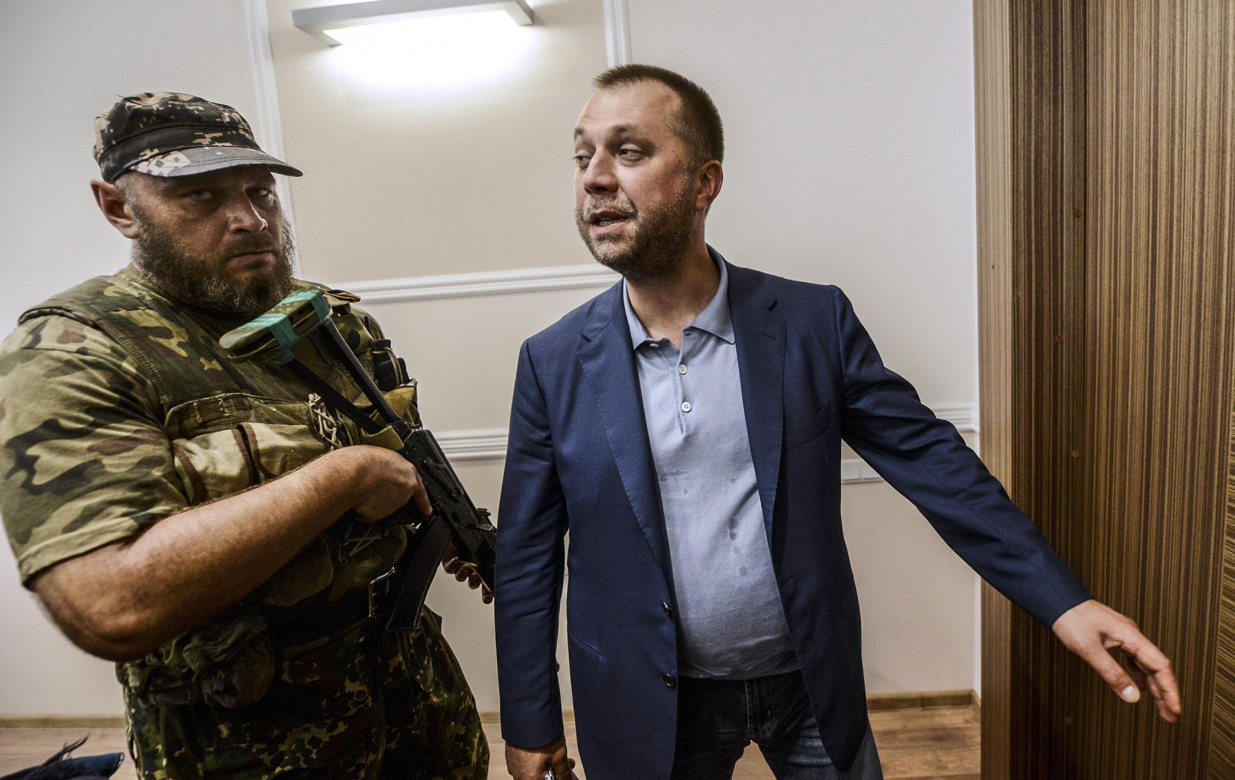 Image: Alexander Borodai stands next to pro-Russian separatist in military fatigues