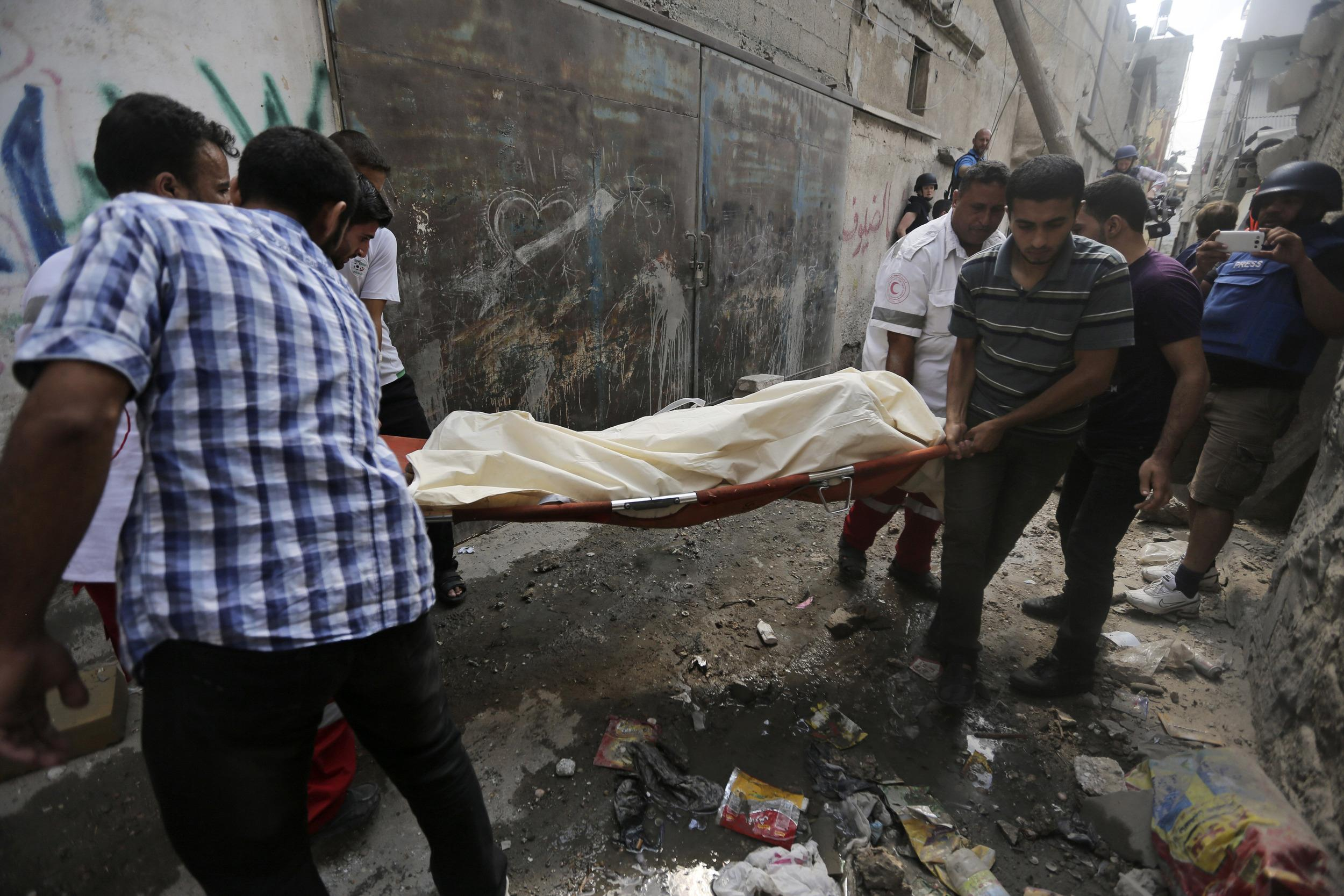 Image: Palestinians carry a dead body found in the rubble of a home destroyed by an Israeli strike in Gaza City on Sunday
