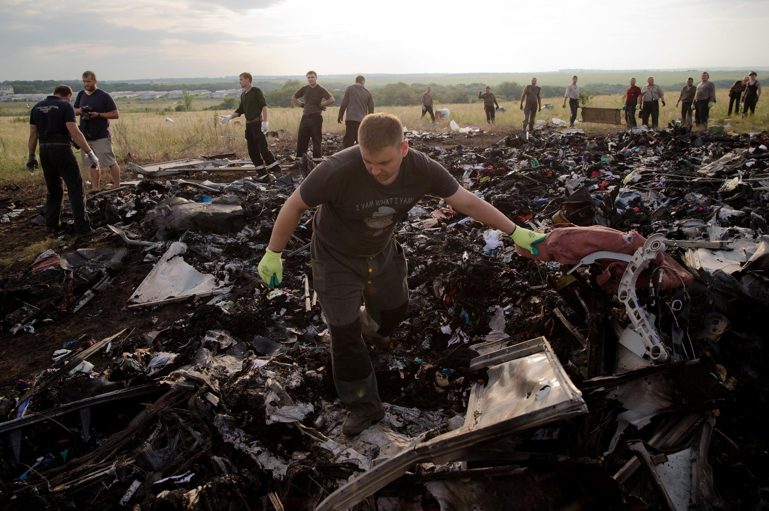 Image: A man looks for the remains of victims in the debris at the crash site