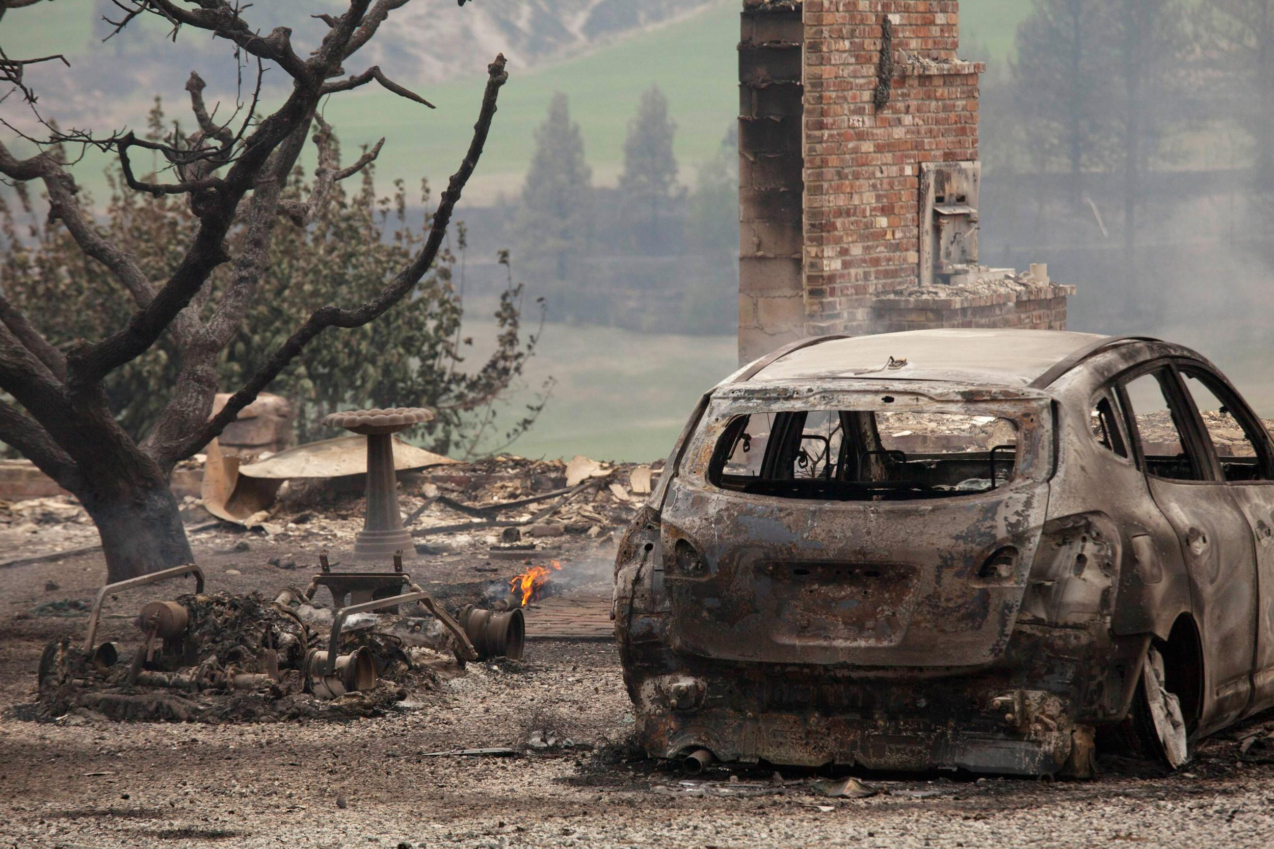 Image: A burnt car is pictured near Alta Lake Golf Course after much of the area was consumed by the Carlton Complex Fire near Pateros