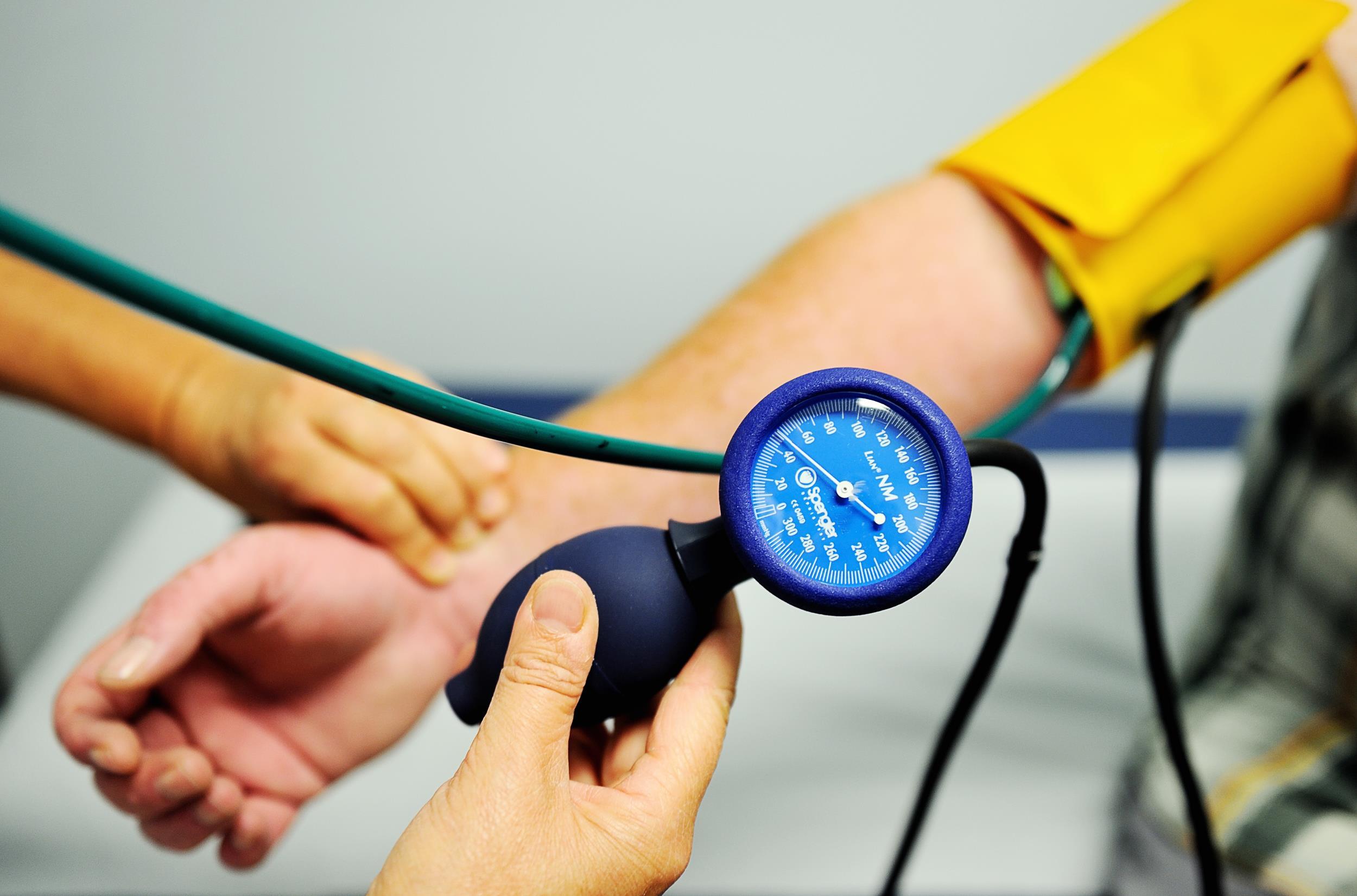 Image: A nurse measures the blood pressure of a patient.