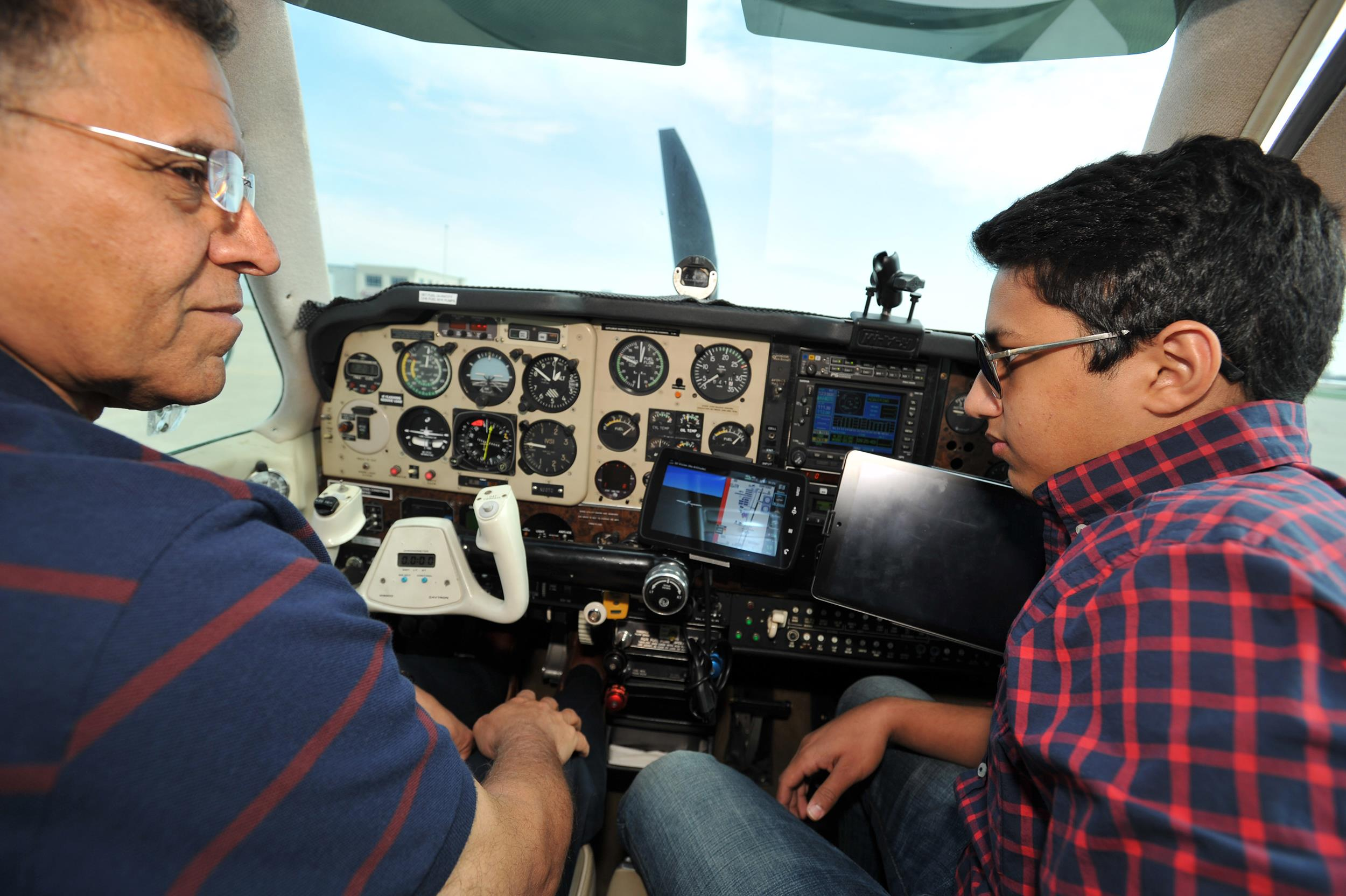 Image: Babar Suleman, left, and son, Haris Suleman, right, sit inside their Beechcraft Bonanza plane