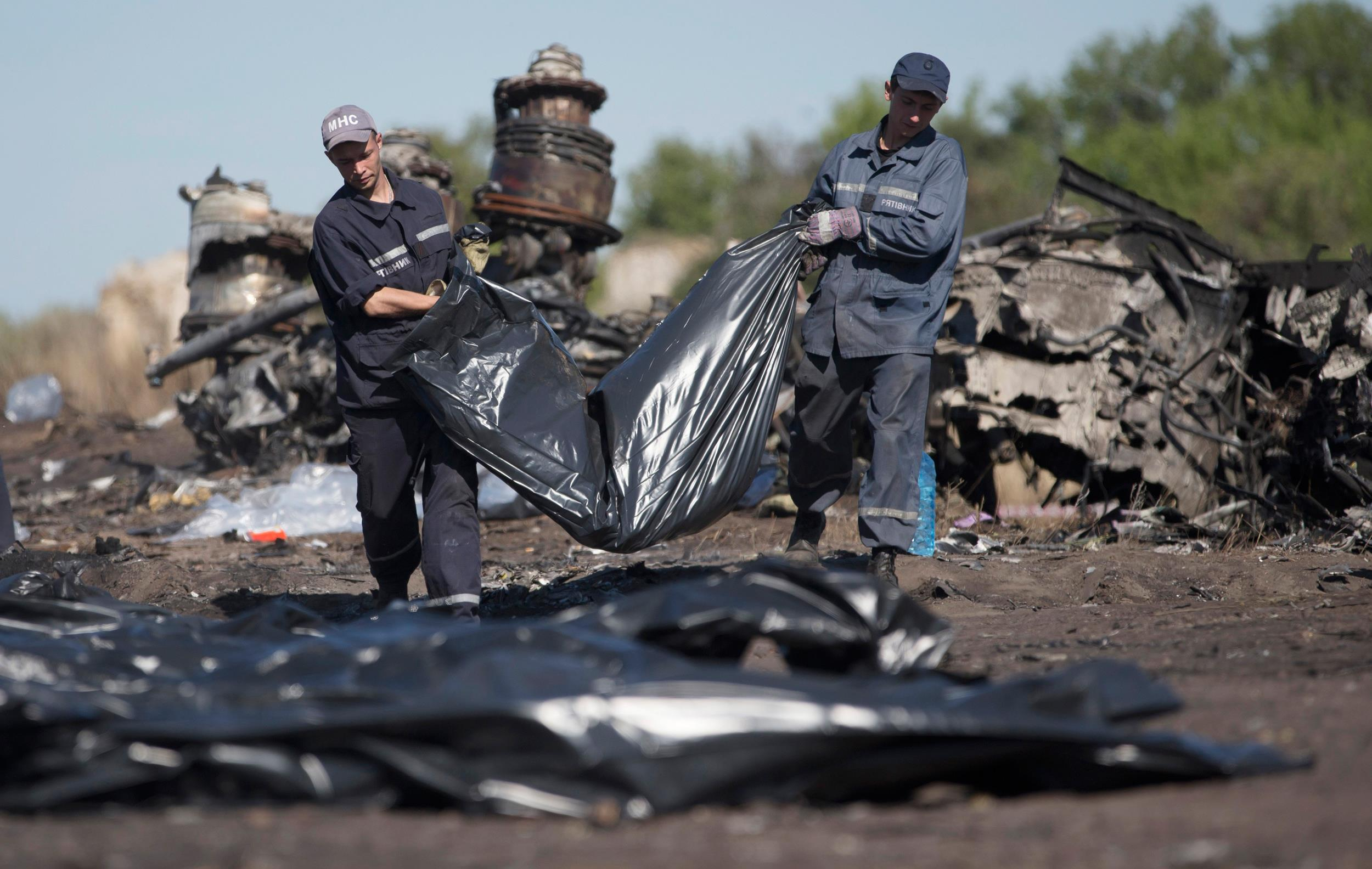 Image: Ukrainian emergency workers carry a victim's body in a bag at the crash site of Malaysia Airlines Flight 17