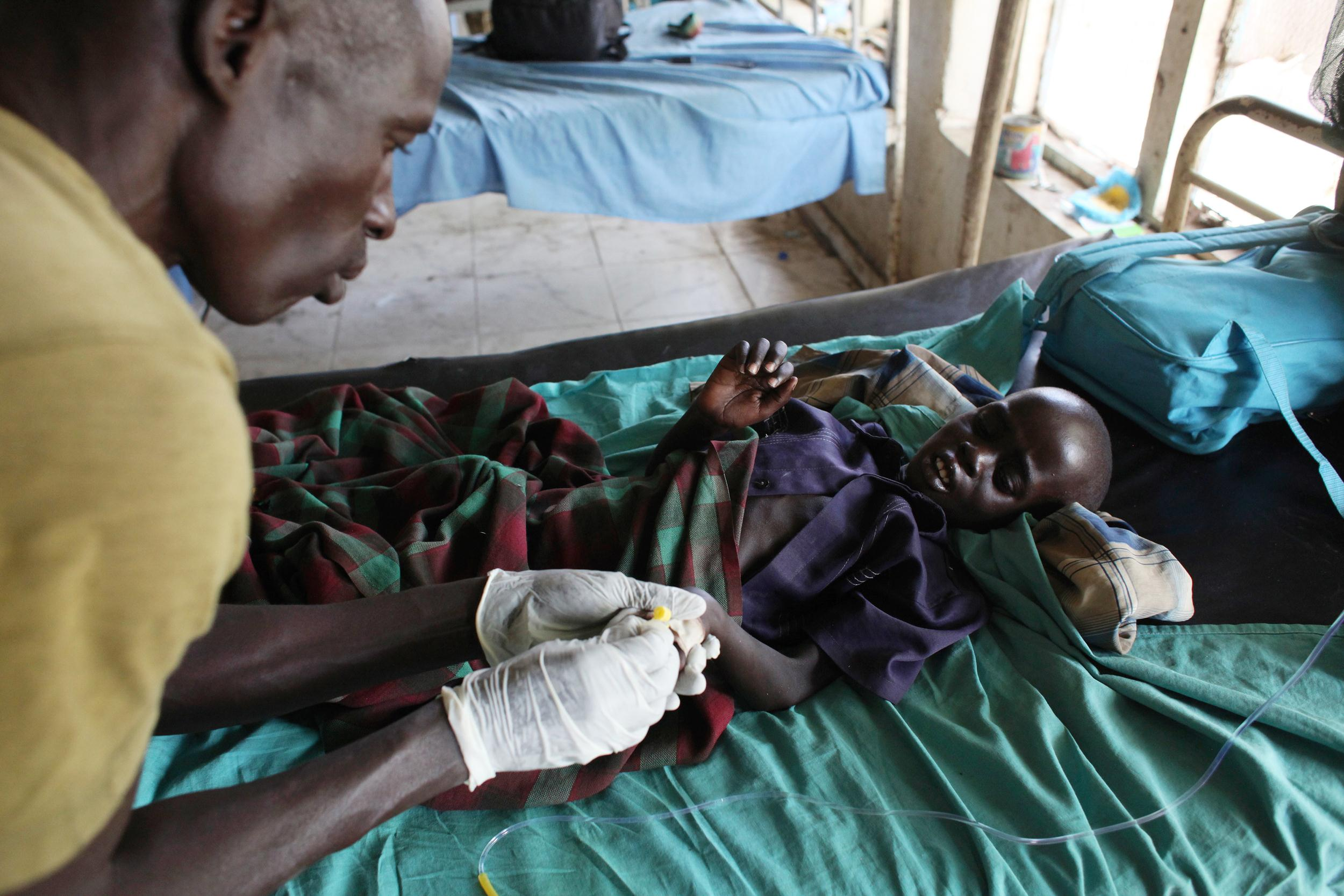 Image: An UPDF medic takes care of a malnourished child with malaria