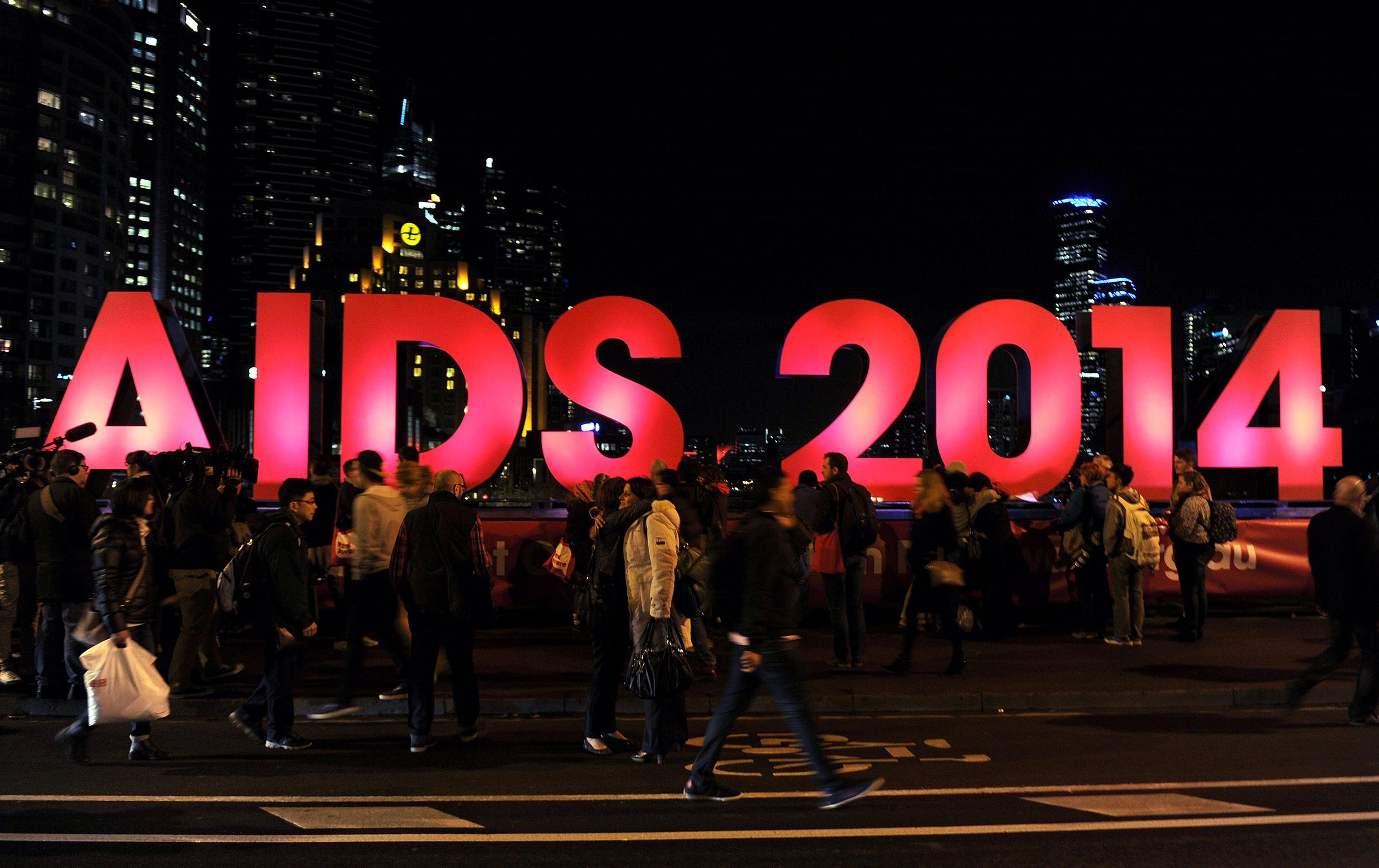 Image: People gather next to a sign reading AIDS 2014 in Melbourne on July 18 after news that downed Malaysia Airlines flight MH17 was carrying many participants headed to the 20th International AIDS Conference planned this weekend in the Australian city.