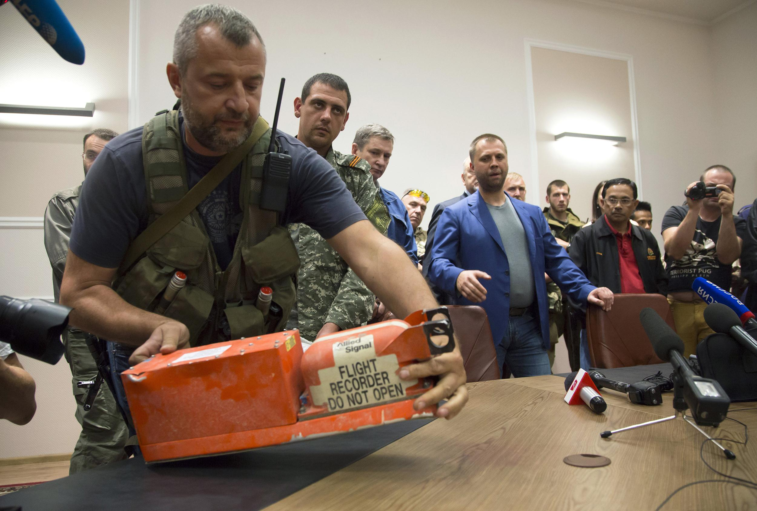 Image: A pro-Russian fighter places a black box from the crashed Malaysia Airlines Flight 17 on a table while handing it over from Donetsk People's Republic officials to Malaysian representatives in the city of Donetsk, eastern Ukraine on July 22.