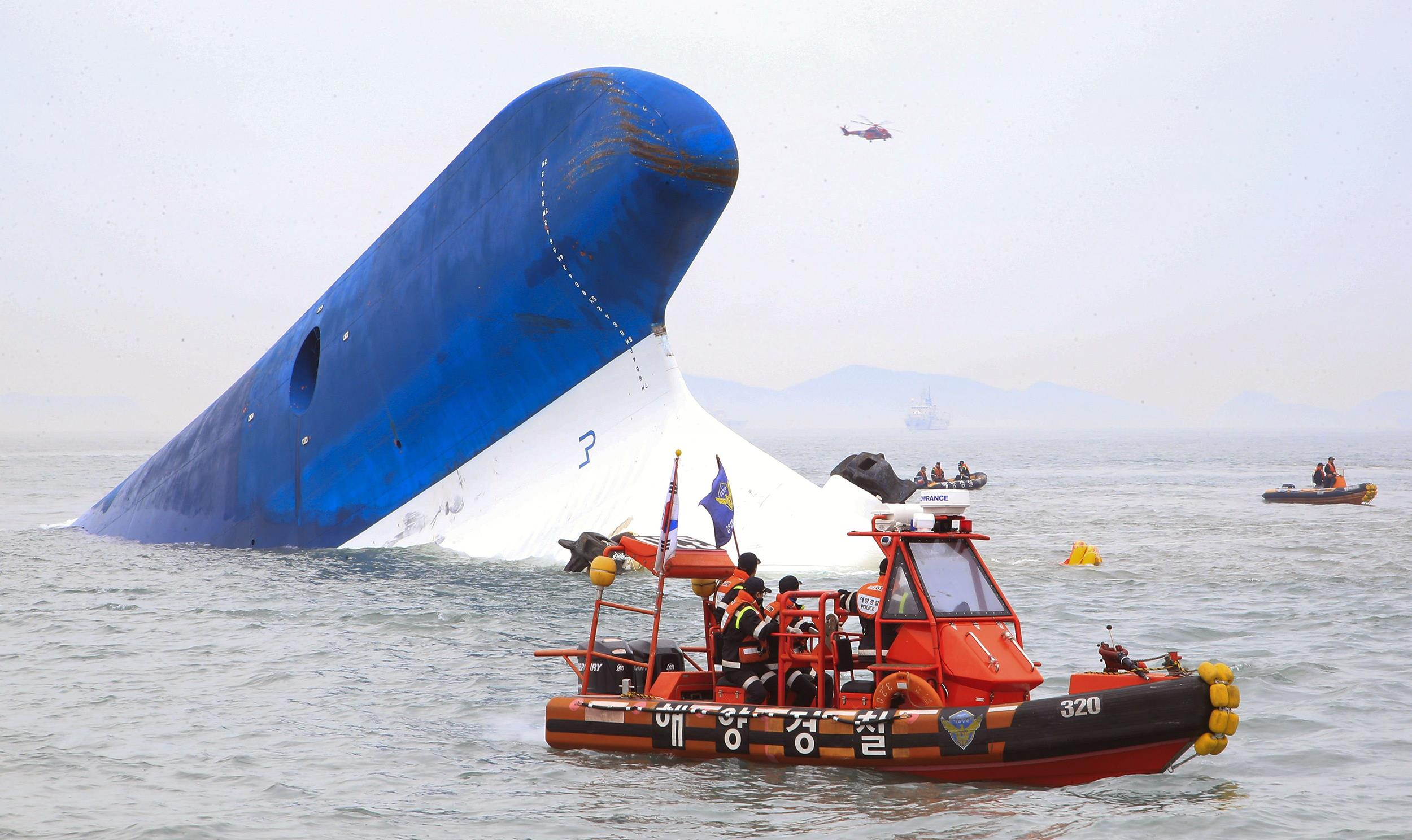 Image: Coast guard members search for passengers near a South Korean ferry (C) that capsized on its way to Jeju island