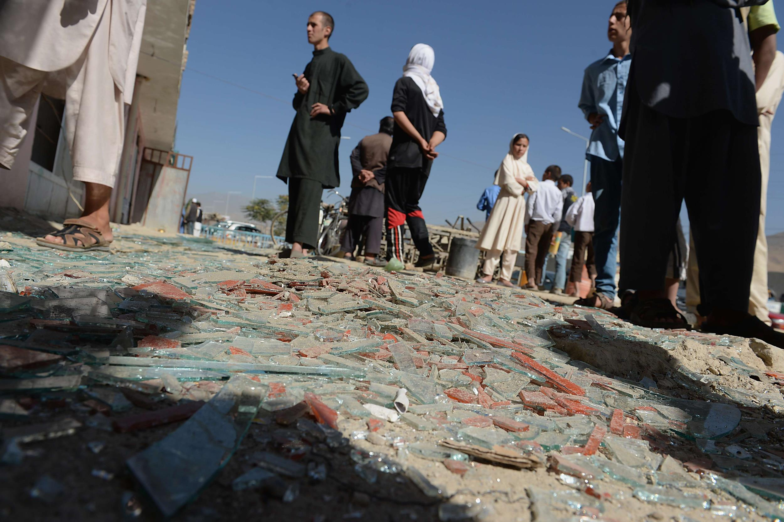 Image: Afghan men look on amid broken glass and debris at the site of a suicide attack in Kabul