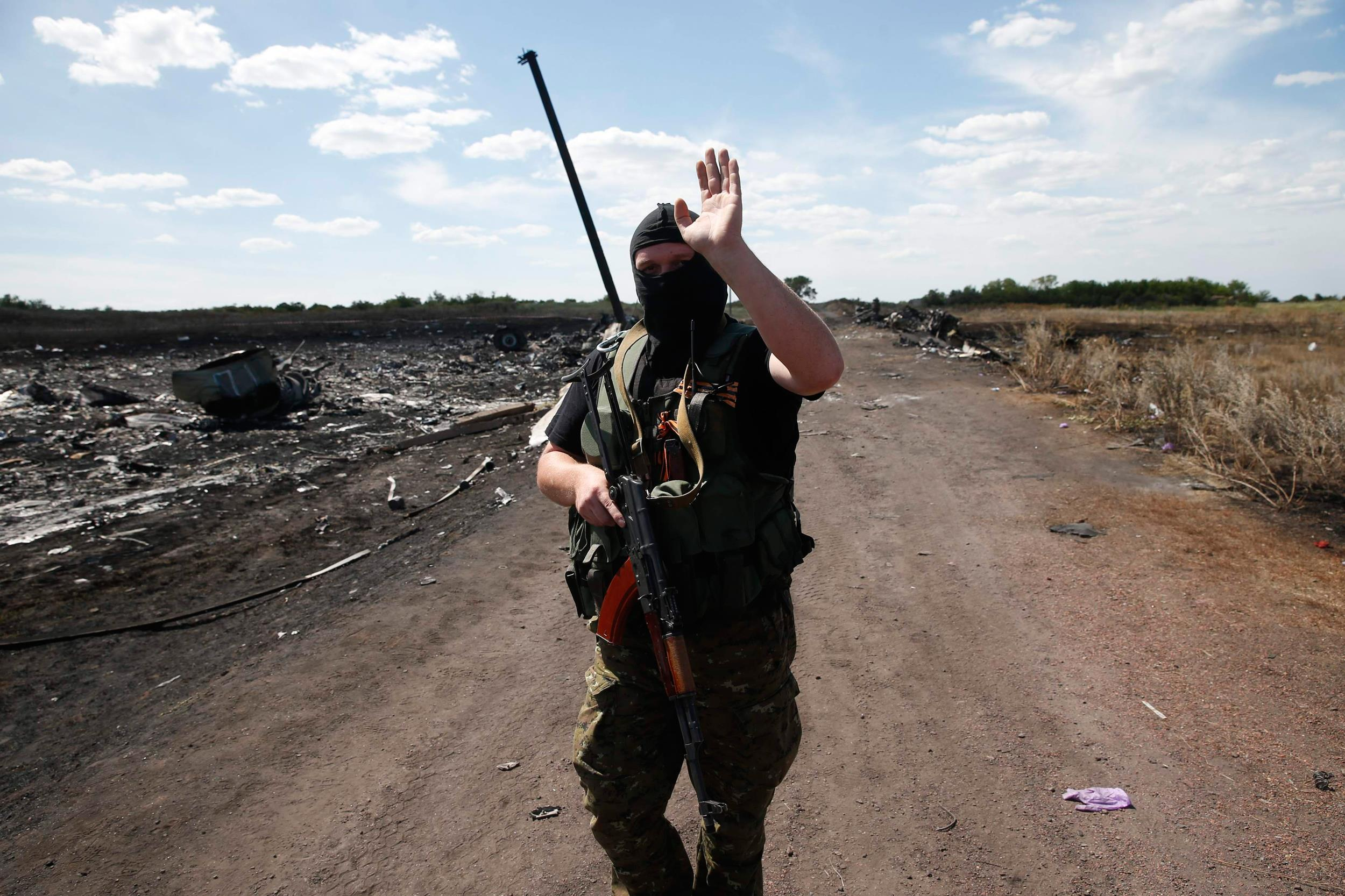 Image: An armed pro-Russian separatist gestures to reporters at the crash site of Malaysia Airlines Flight MH17, near the village of Hrabove